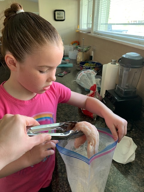 """Now that the oldest is home from school, she finishes up the last part of the chicken, placing it in the flour mixture (which I actually do because she """"can't touch chicken"""" it's grooooossss!"""