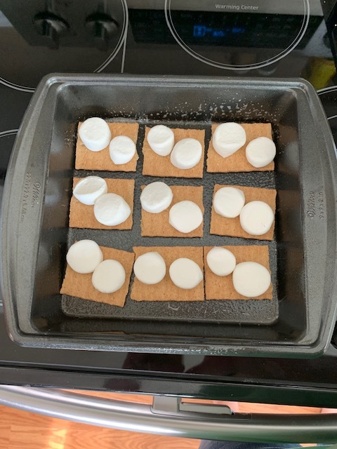 2. Grab your marshmallows and layer them on top of your graham crackers. I cut my marshmallows in half, they seem to stay put better and melt better. If you like gooey, add more marshmallows than I did in my picture.
