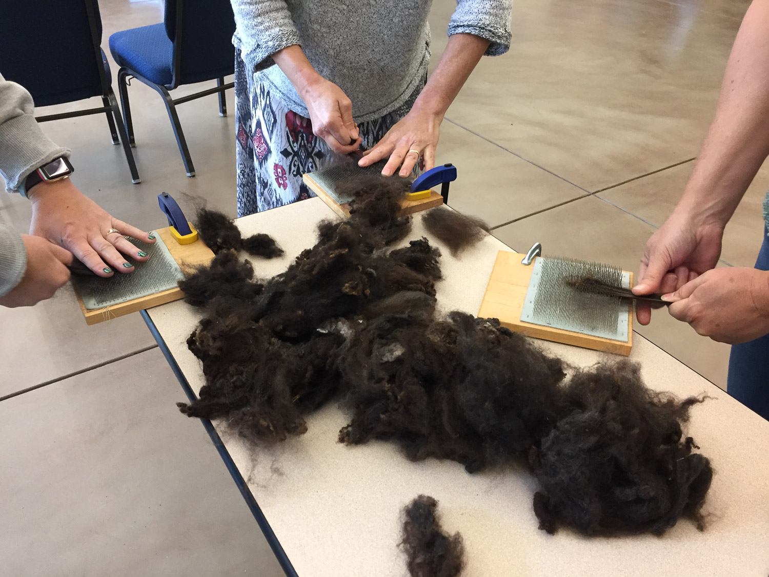 Prepping wool for spinning.