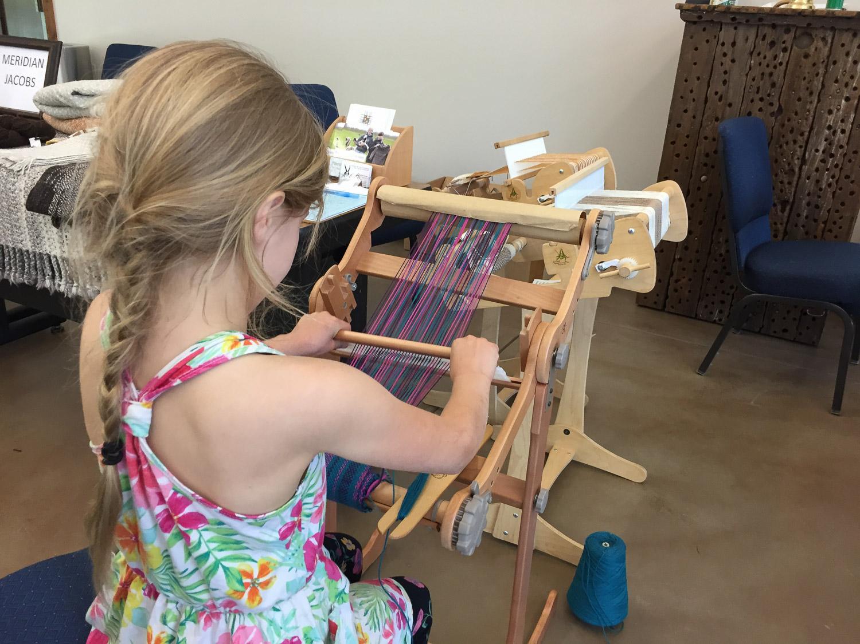 Child working on rigid heddle loom.