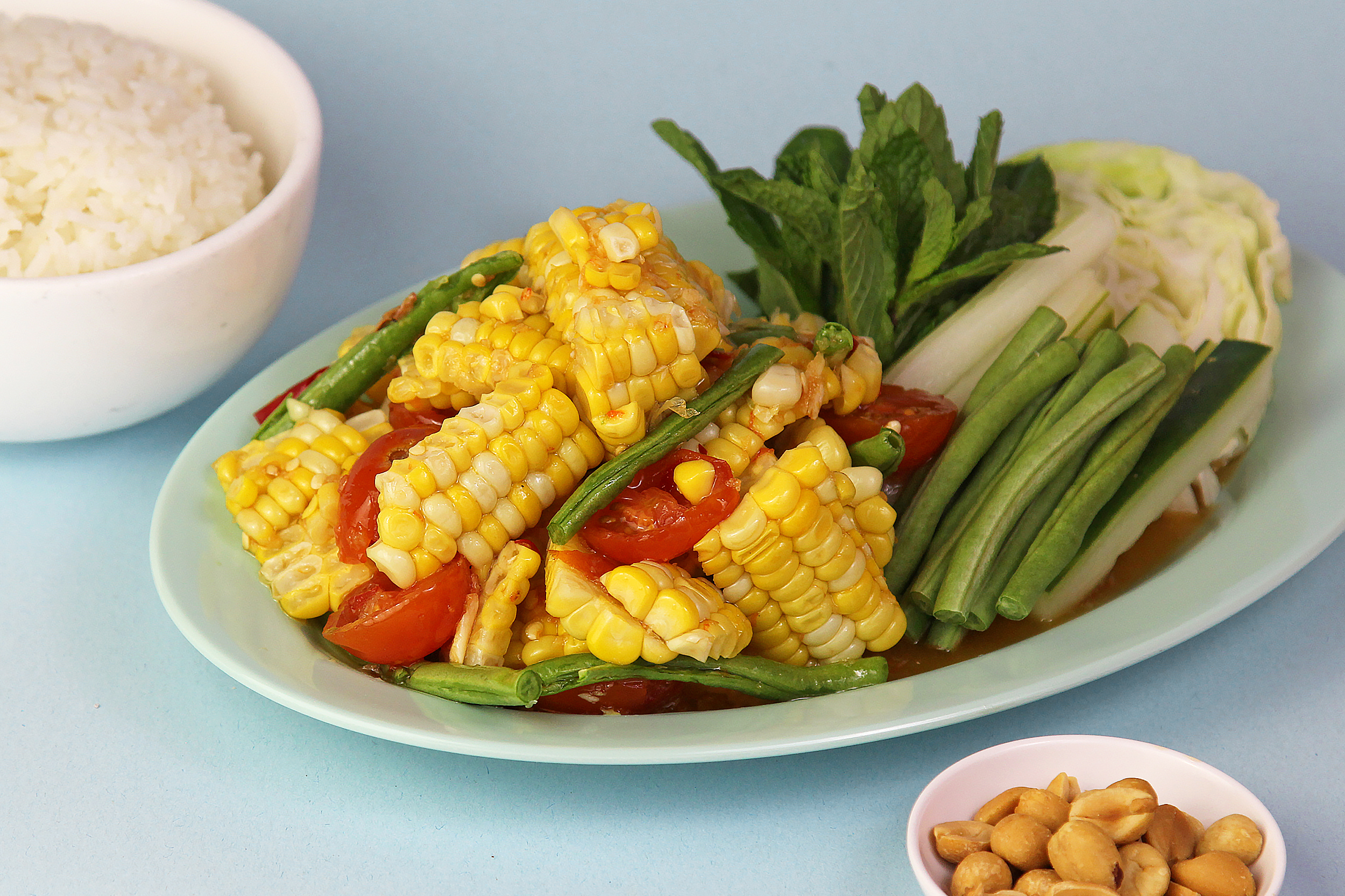CORN SALAD 🌶 (Gluten-Free)   Steamed corn, long bean, cherry tomatoes, garlic, Thai bird's eye chili, peanuts  11