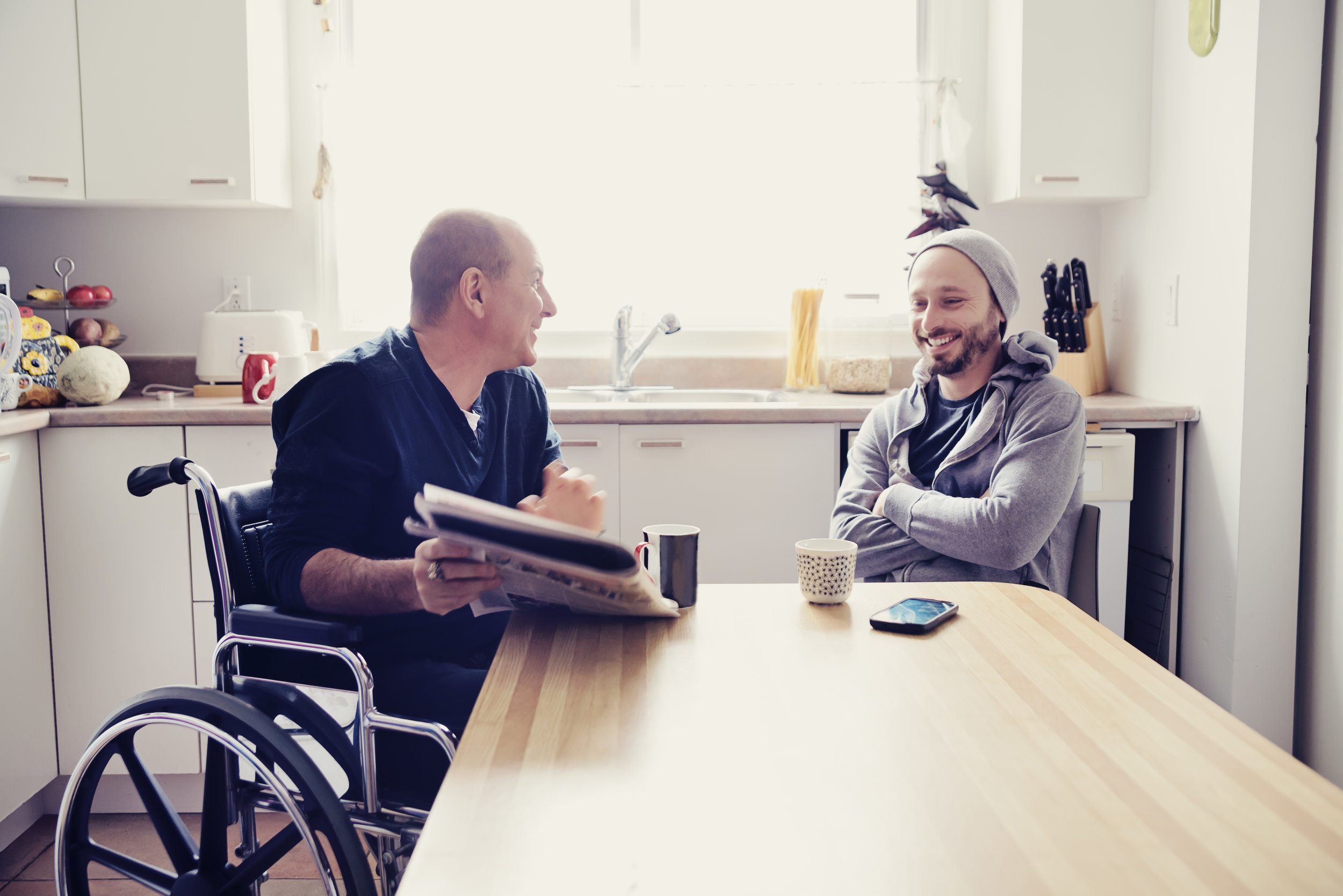 Man on a wheelchair talking and smiling to young man
