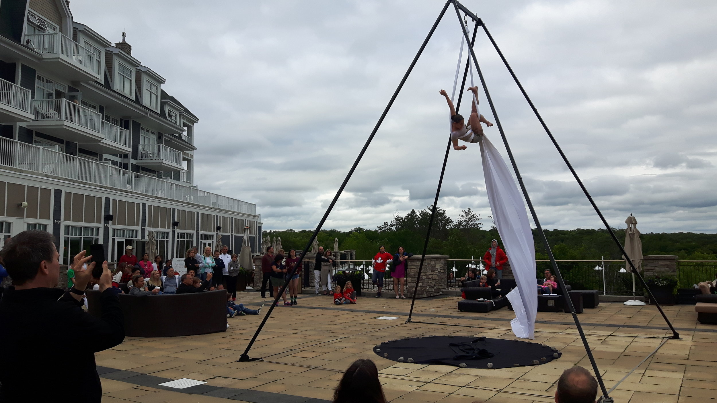 Performer climbing white silks outdoors in wind