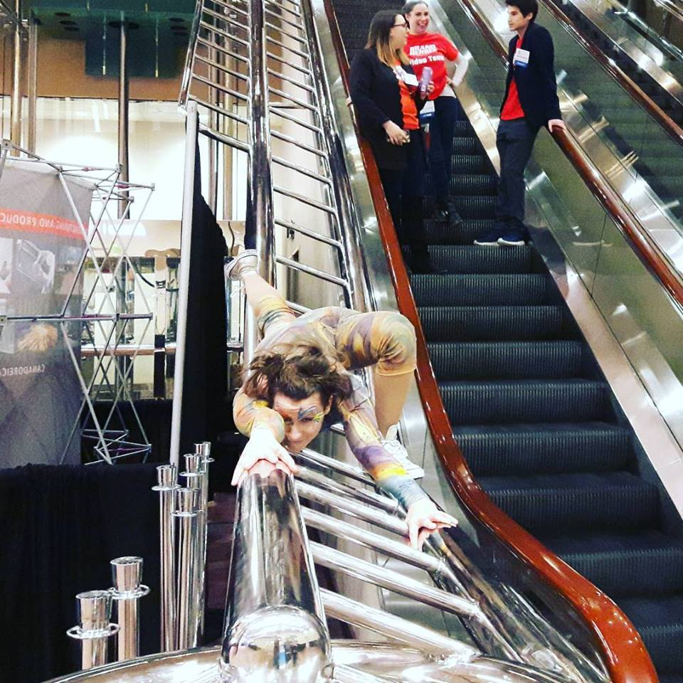 Contortionist in colourful costume lying across escalator railing
