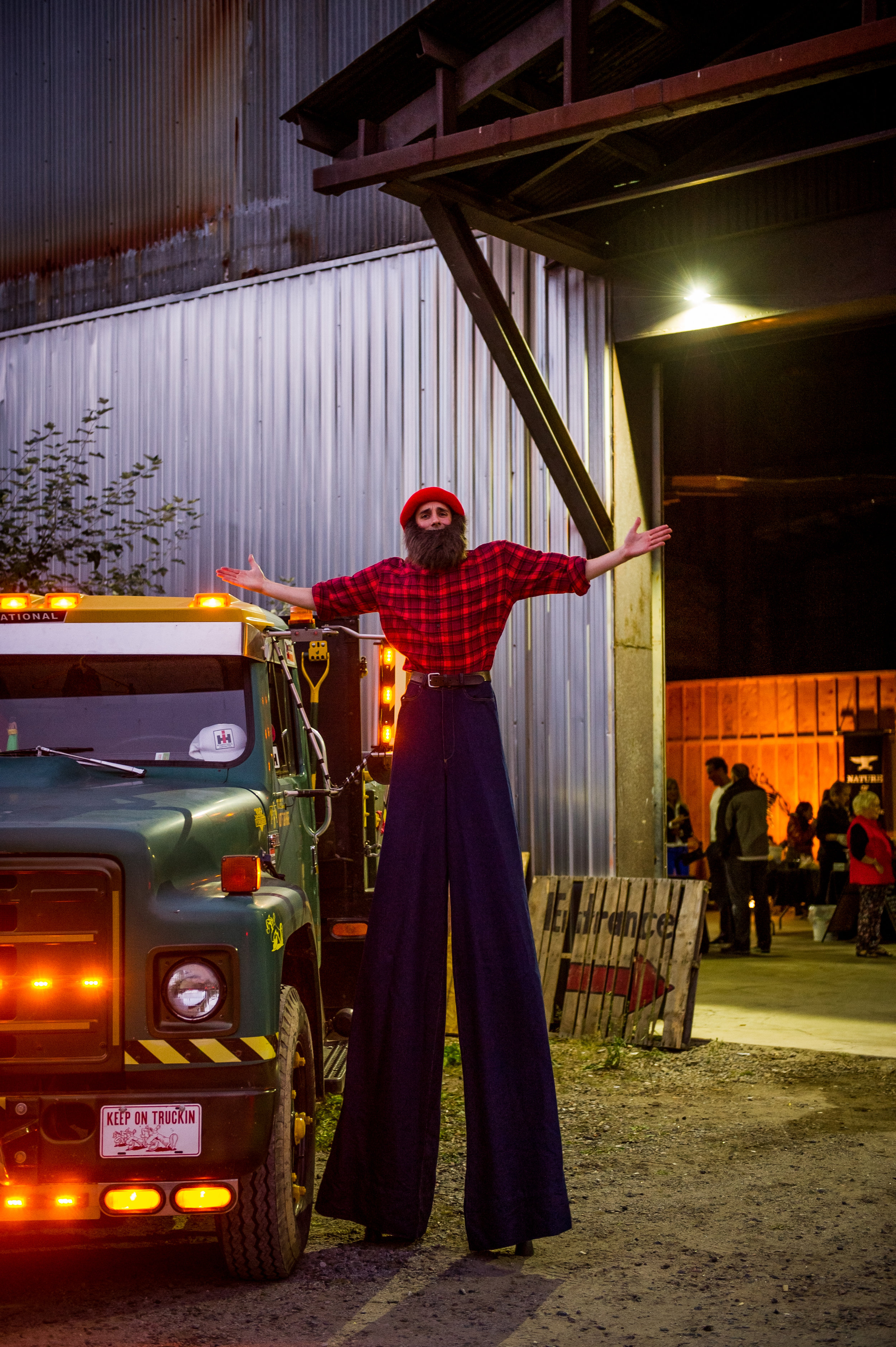 Nine-foot lumberjack on stilts with old truck and foundry