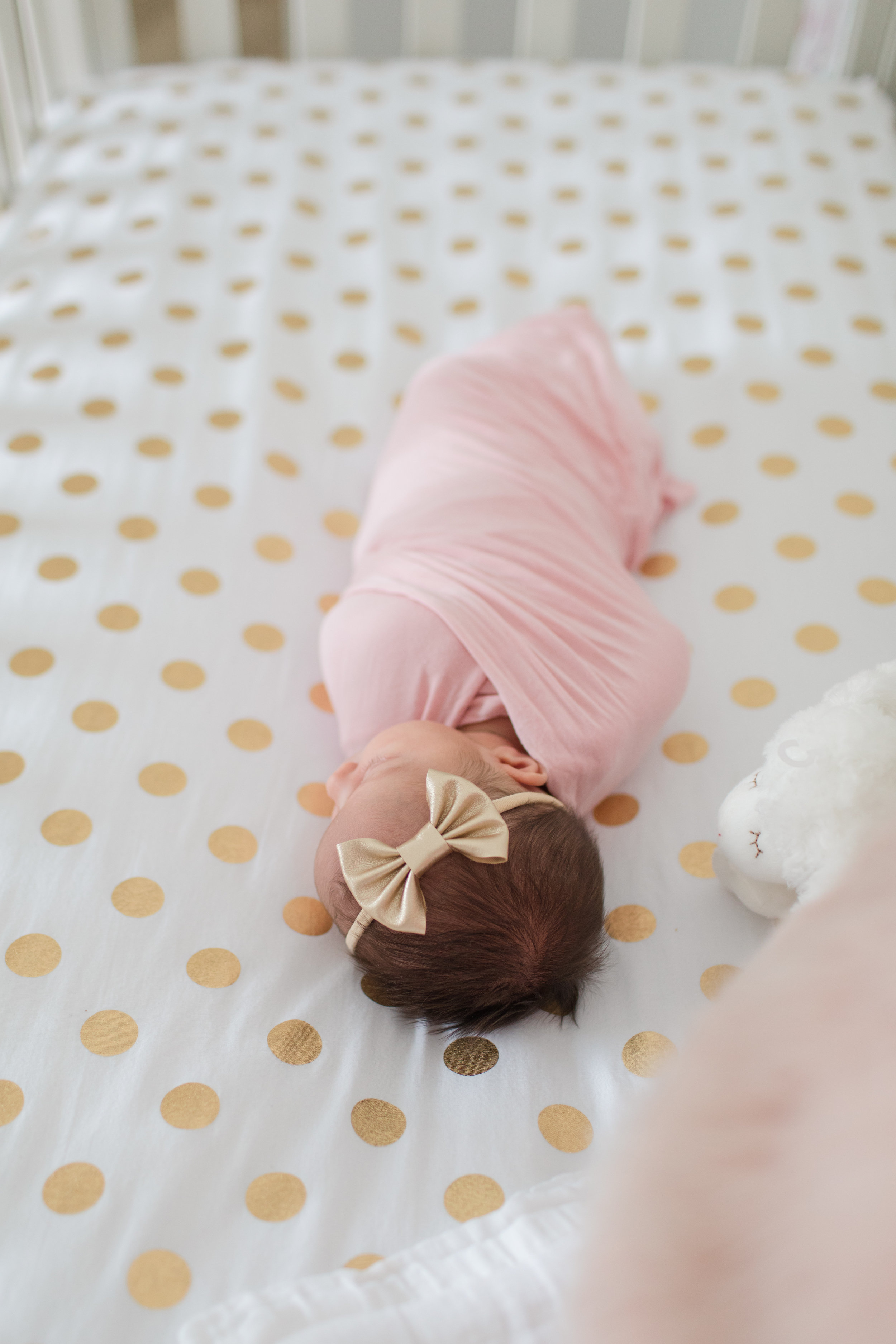 Lifestyle Newborn Baby Girl in her Gold and White Crib