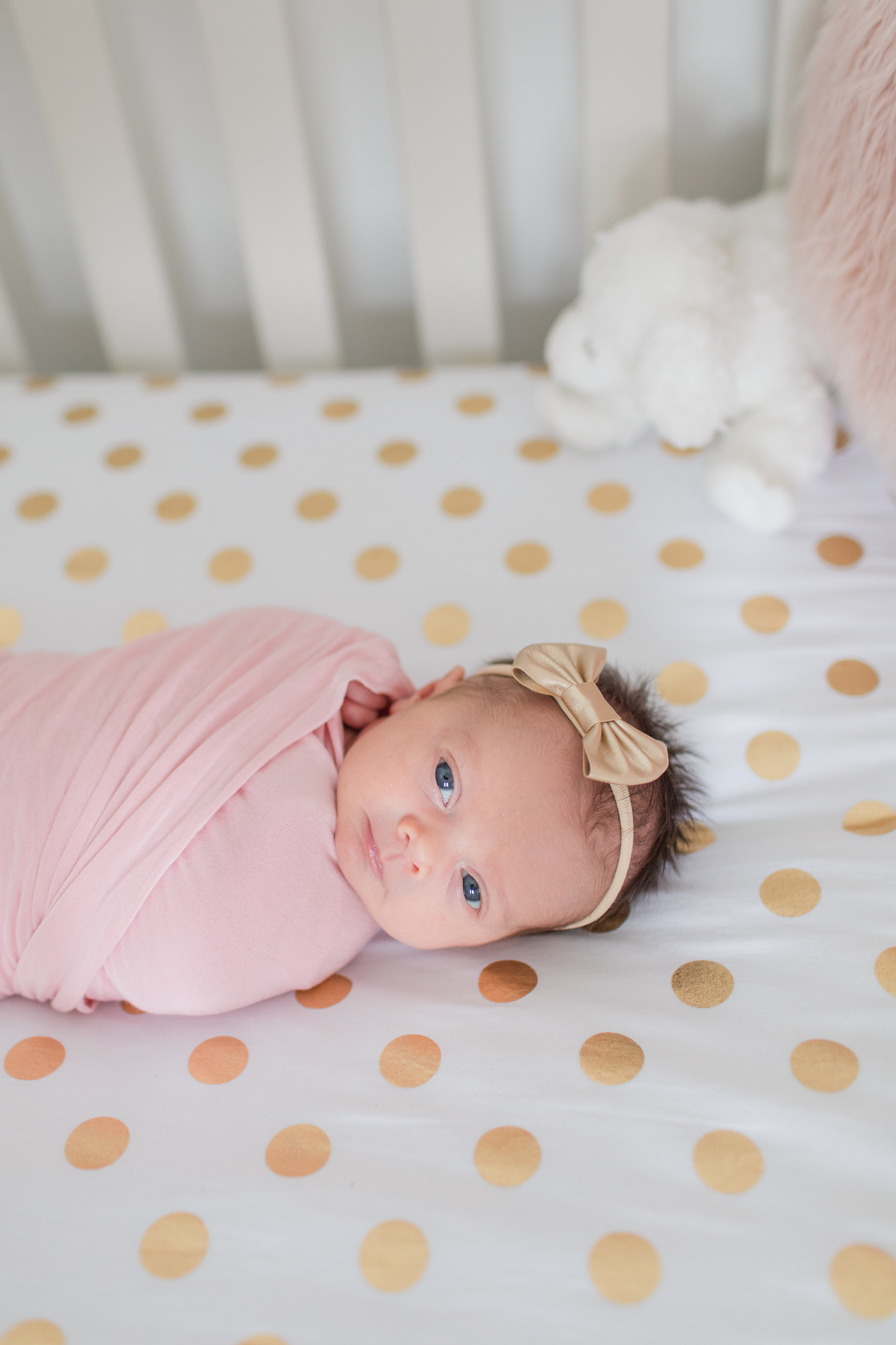 Newborn Baby Girl in a pink swaddle in her crib