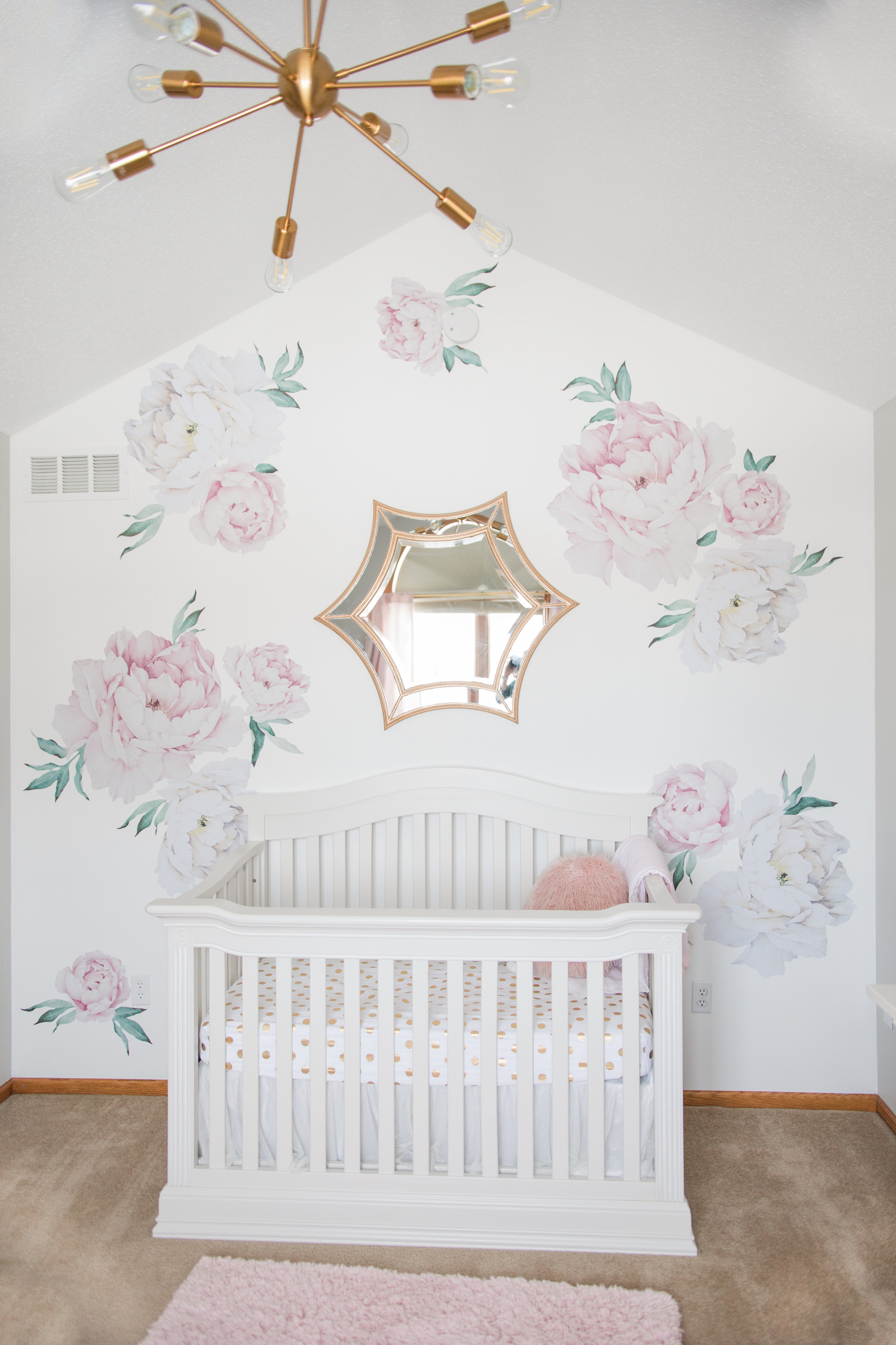 large pink and white floral accent wall in a baby girls nursery