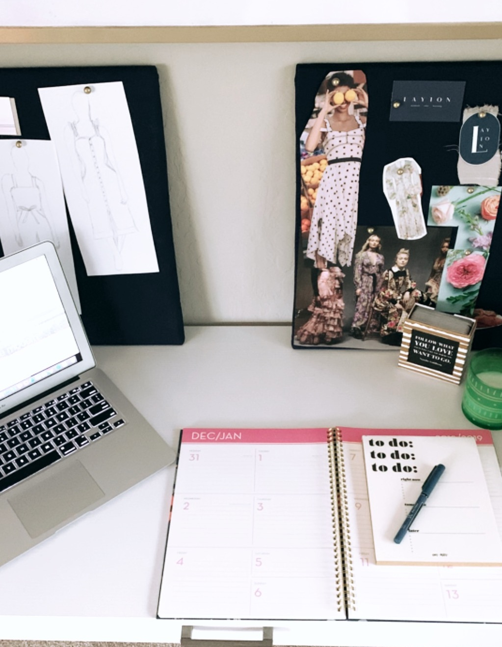 A photo of a work desk including a planner, calendar and laptop.