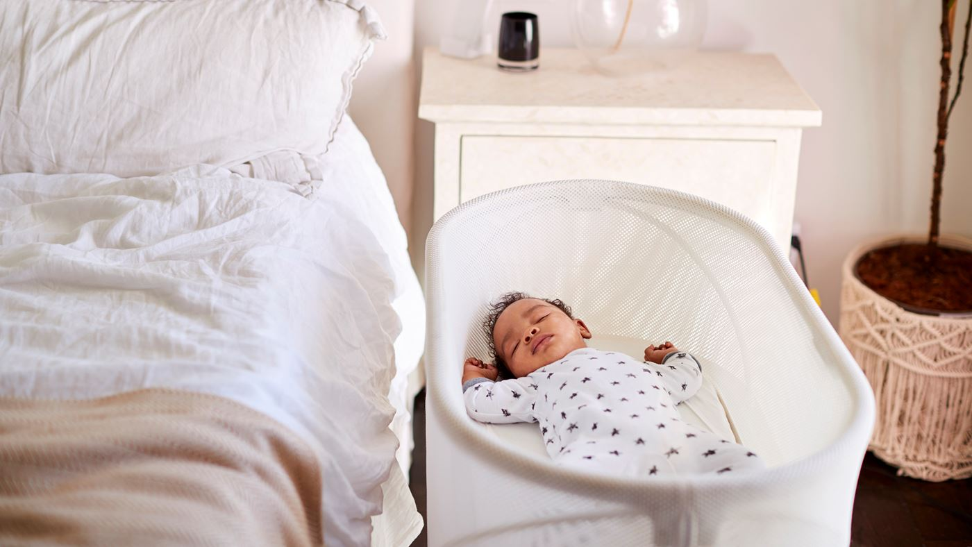 A sleeping baby in a bassinet next to a bed.