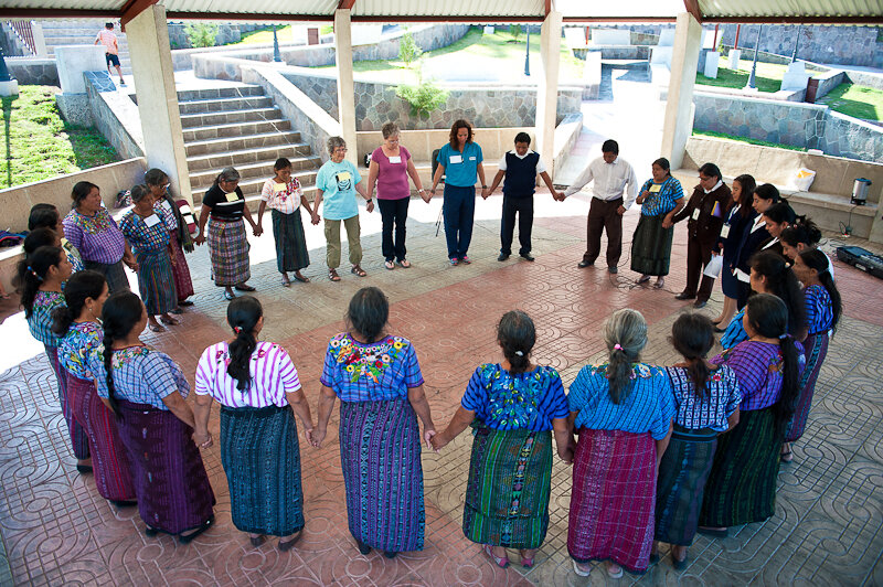 A group of Guatemalan women and care providers holding hands in unison.