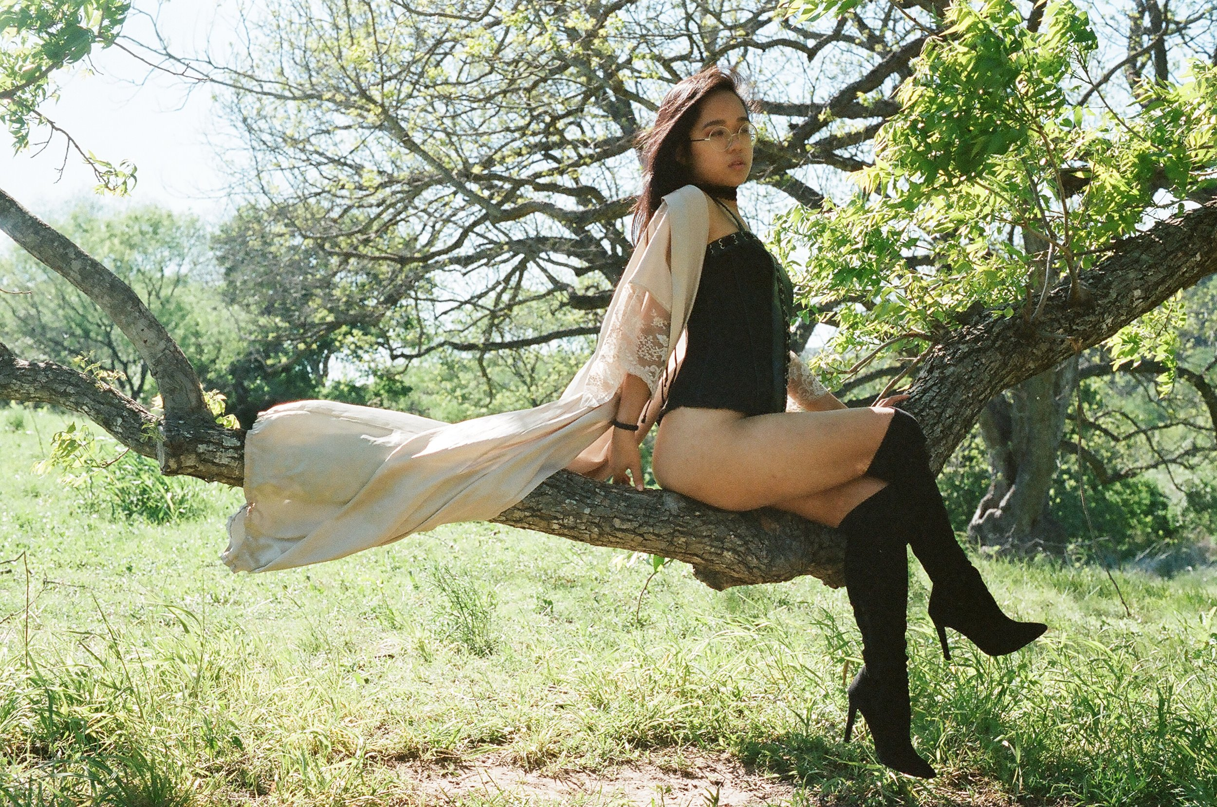 Asian femdom Empress Wu in a corset and thigh high boots sitting on a branch of a tree on a hot Texas day