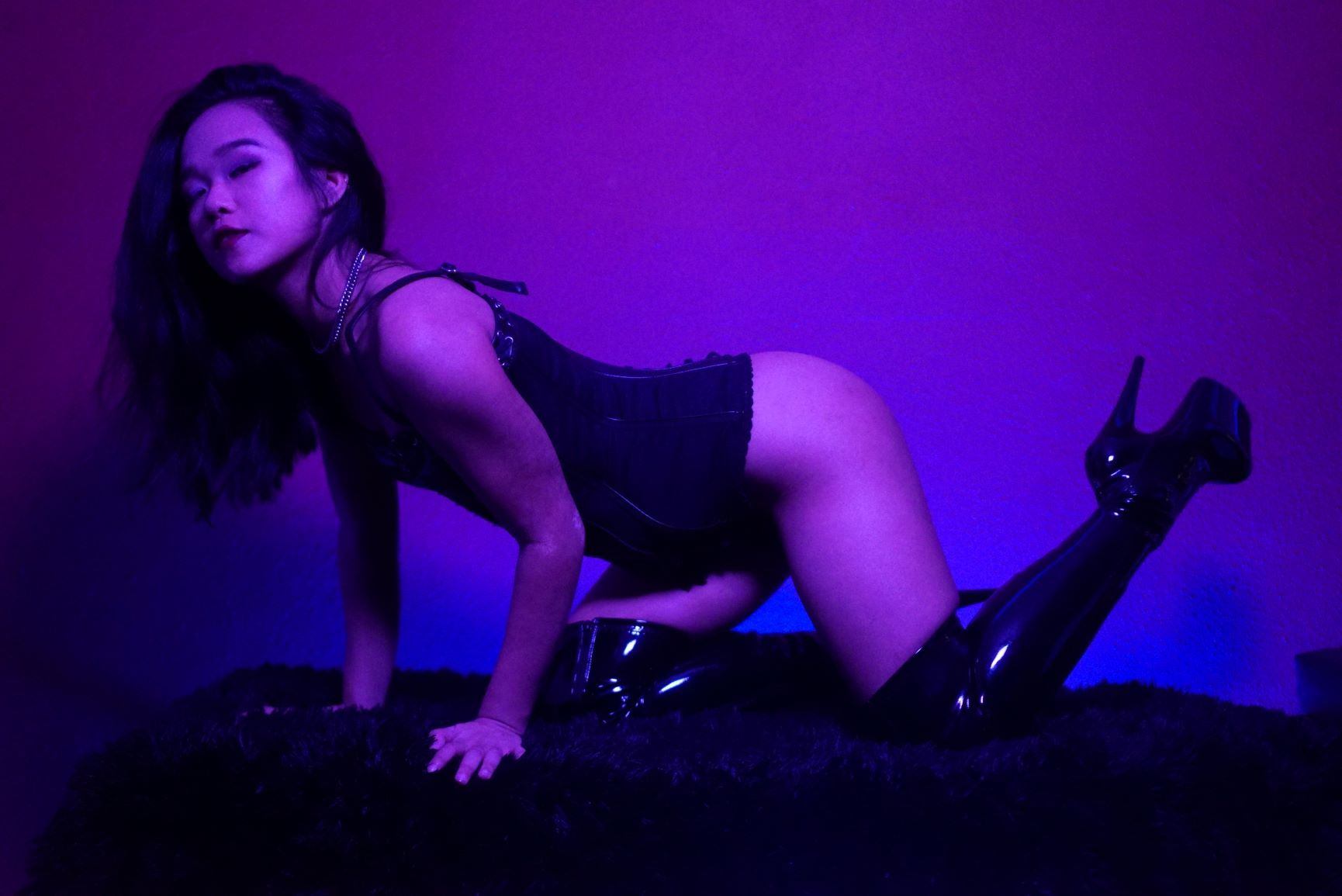 Asian New York prodomme Empress Wu in a leather corset and vinyl boots, waiting to pounce on you.