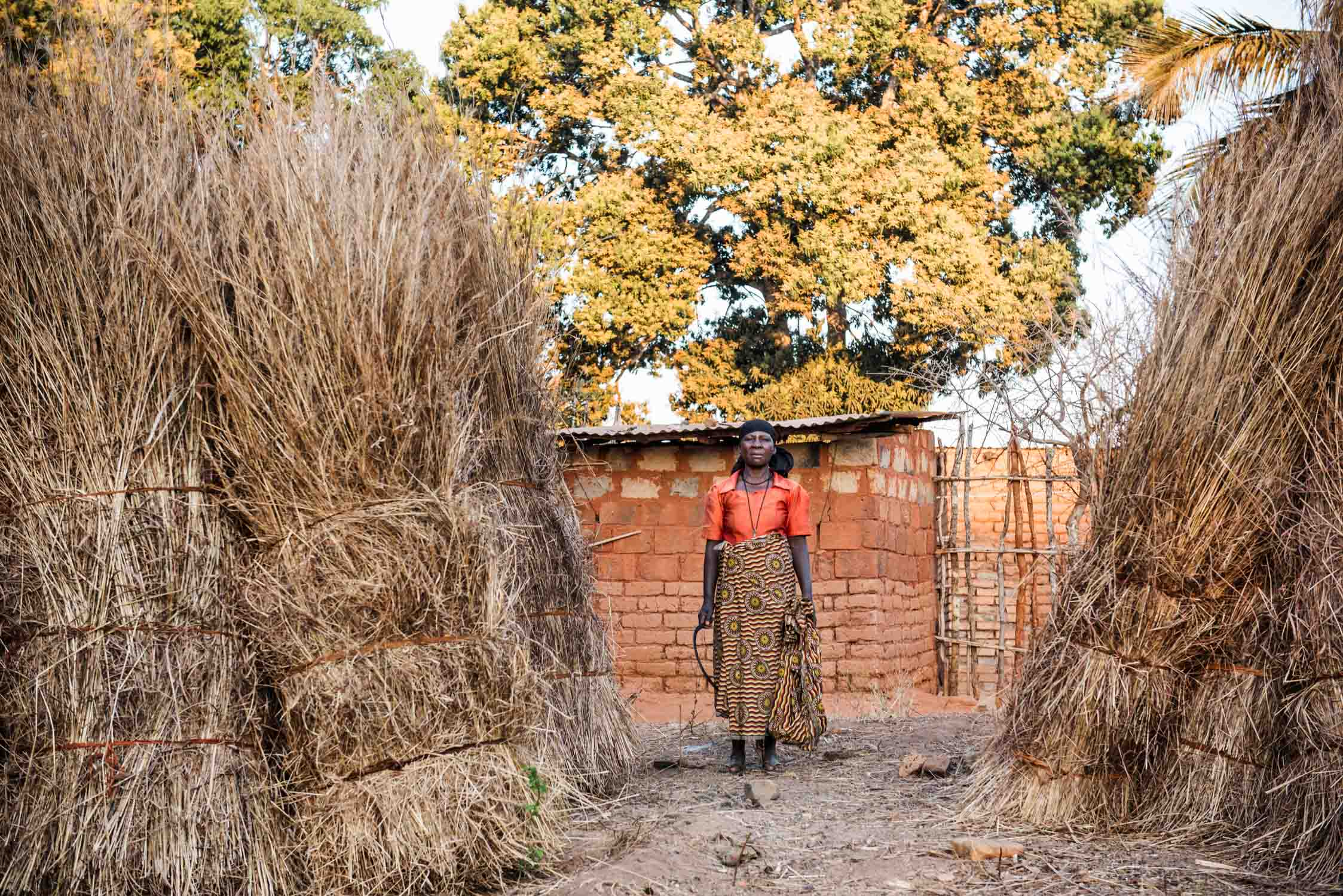A woman of Likuyu village with her harvest. The grass is mainly used to build traditional houses.