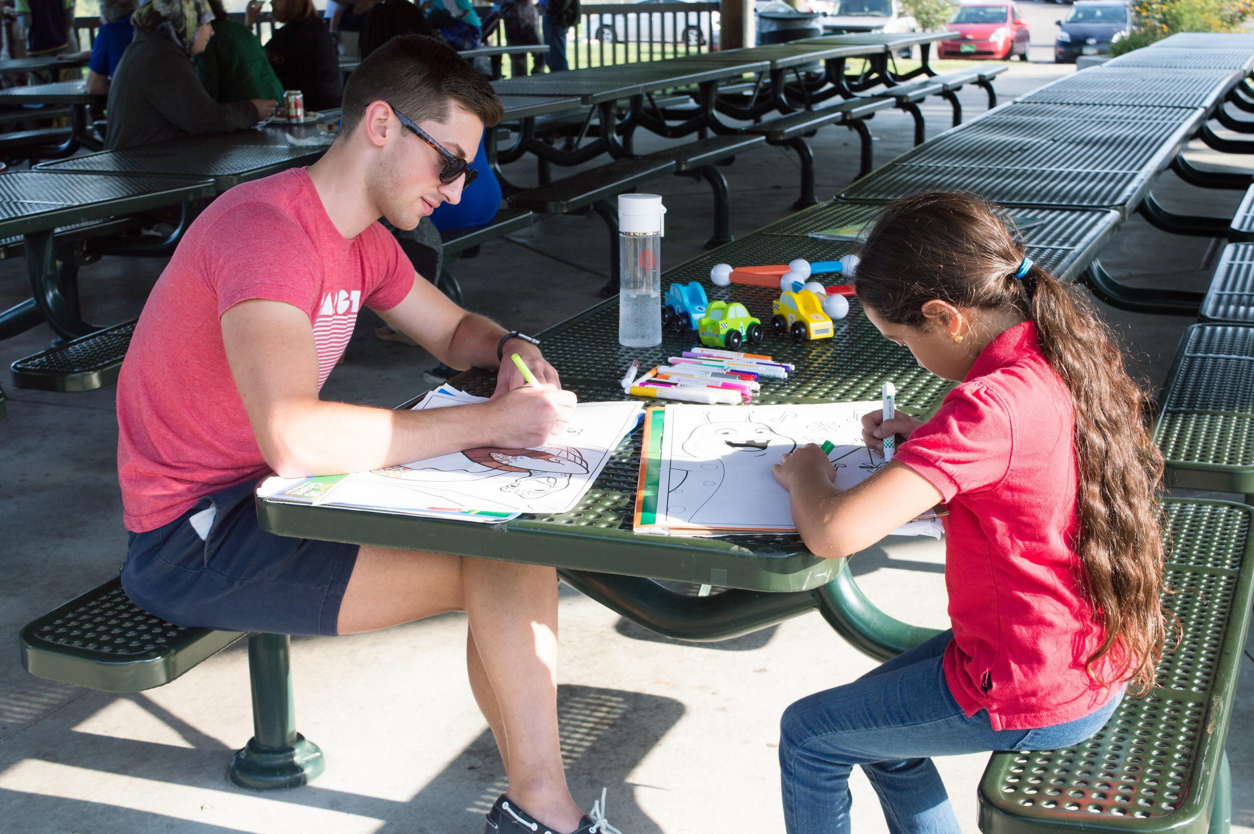رجل و طفل يكتبون على الطاولة