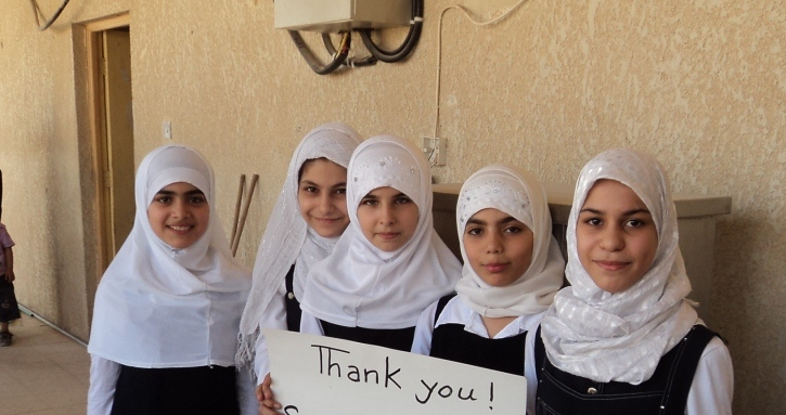 Iraqi girls holding thank you sign for Water for Peace filter