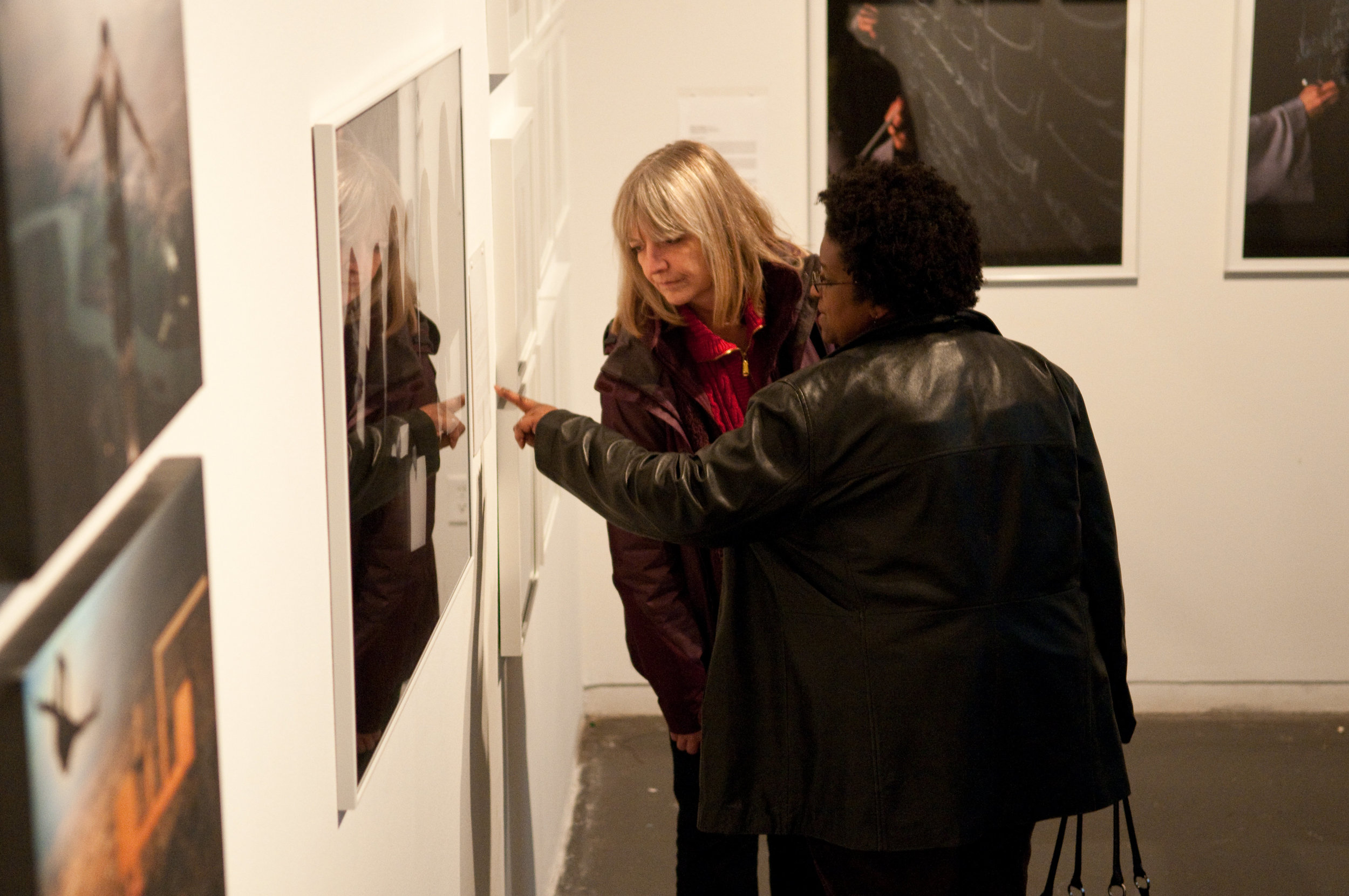 Two women viewing the Not about bombs artwork display