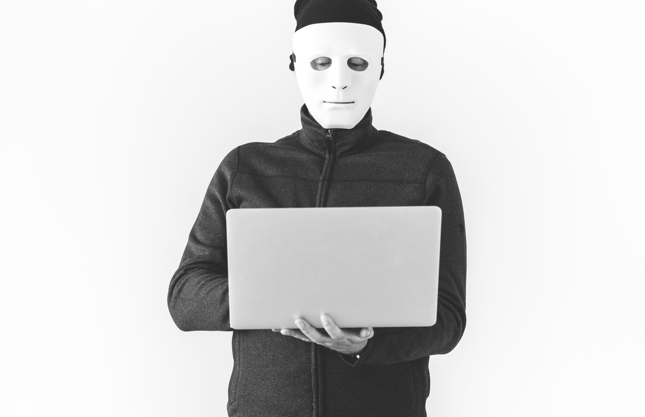 masked man behind laptop.jpeg