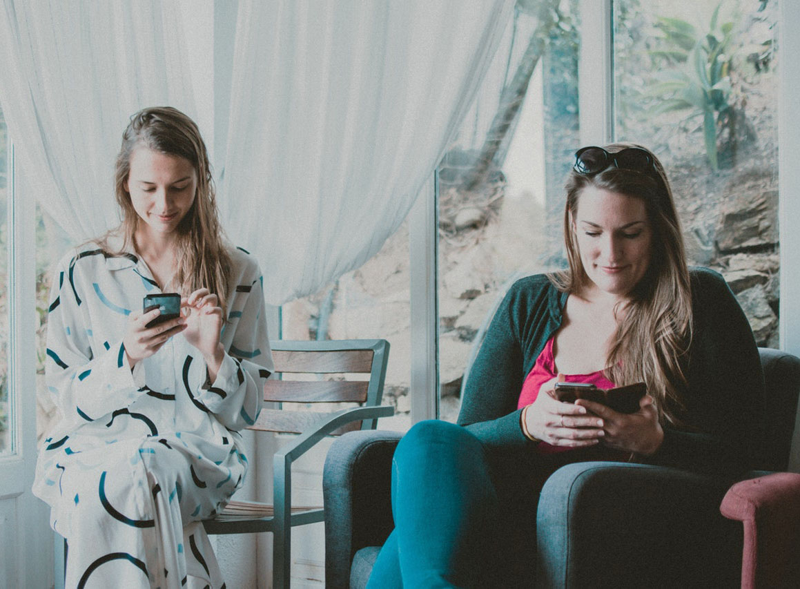 two seated women looking phones.jpg