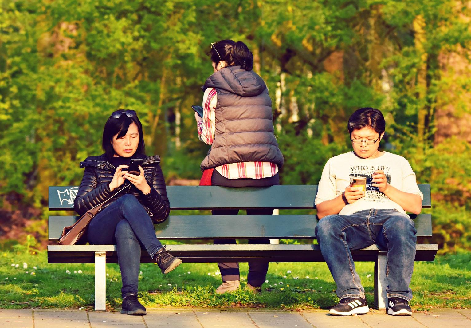 people using smartphone on bench.jpg