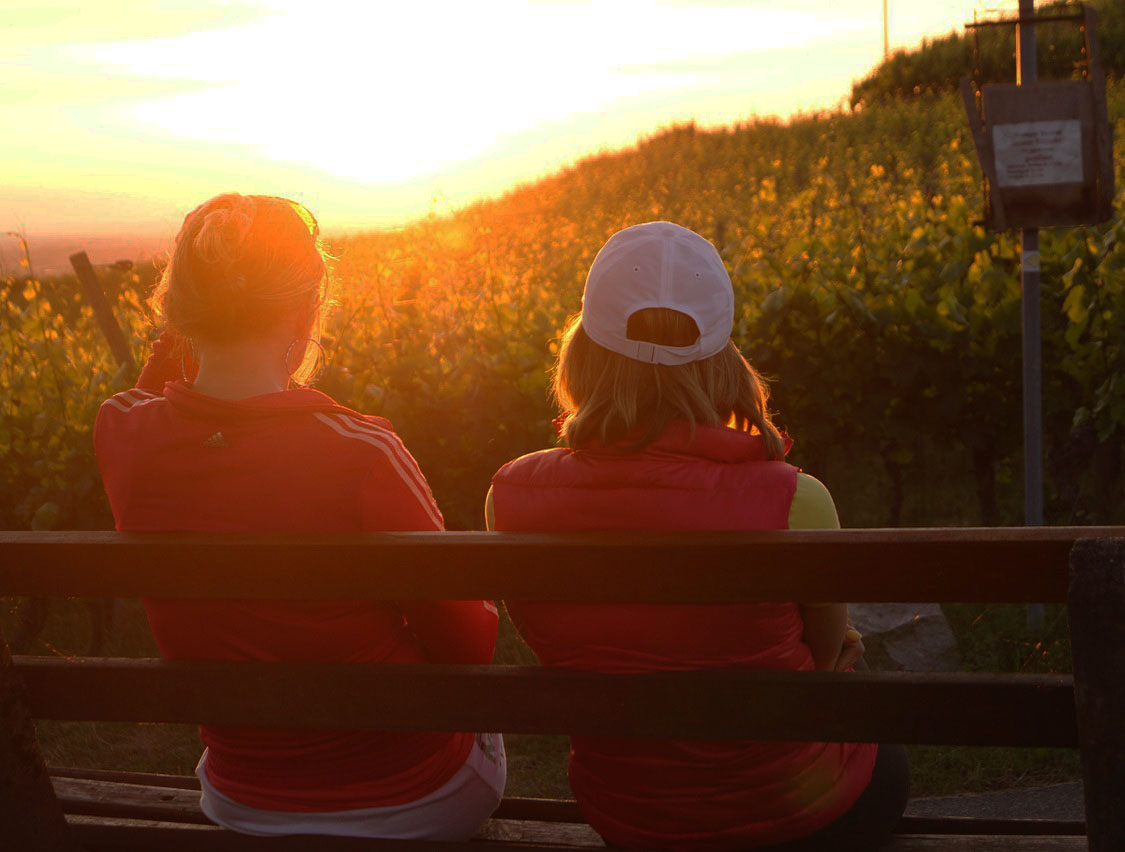 two femal friends sitting together watching sunset.jpg