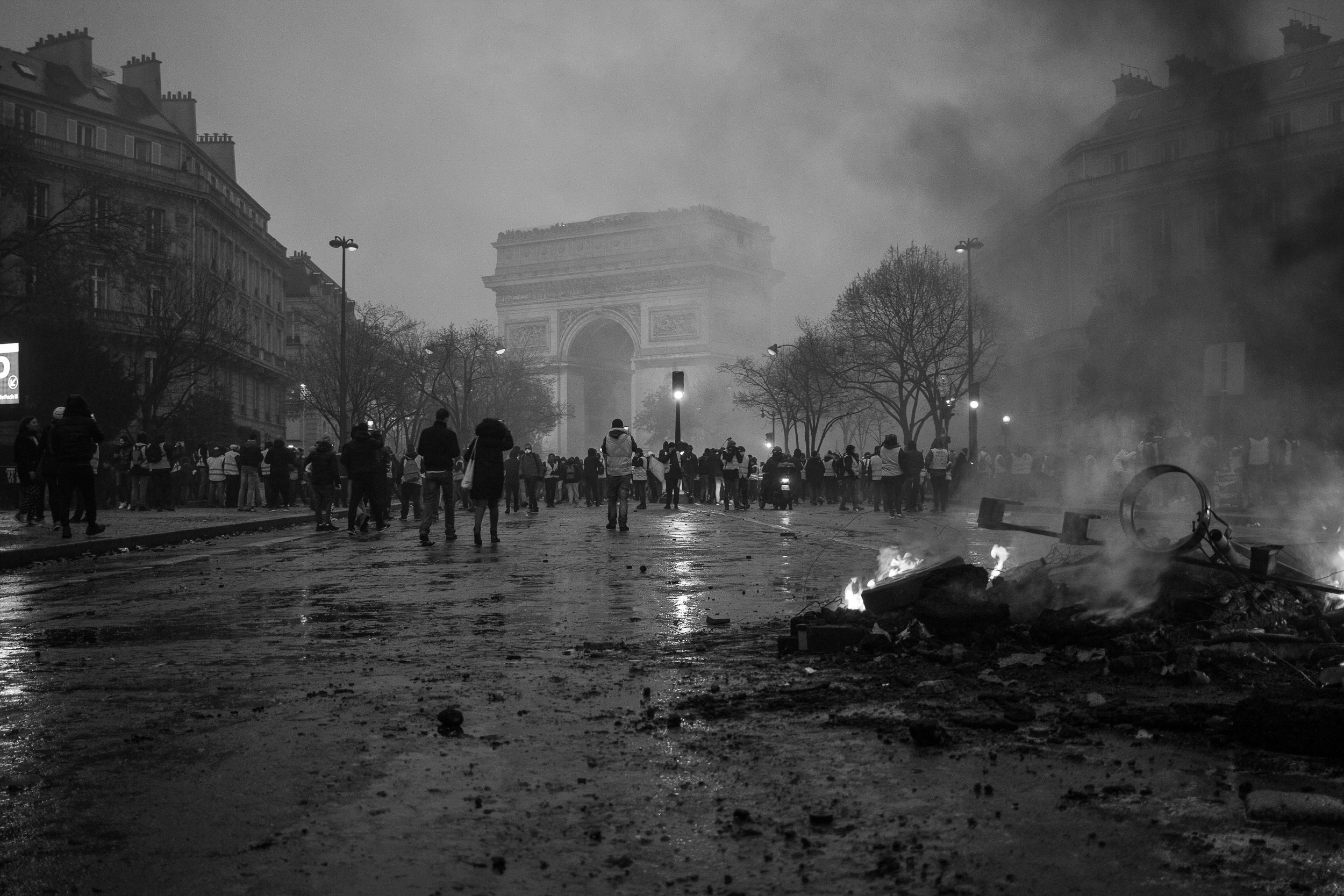 Protesters and rioters demonstrate among burning wreckage near the Arc de Triomphe. (flickr)