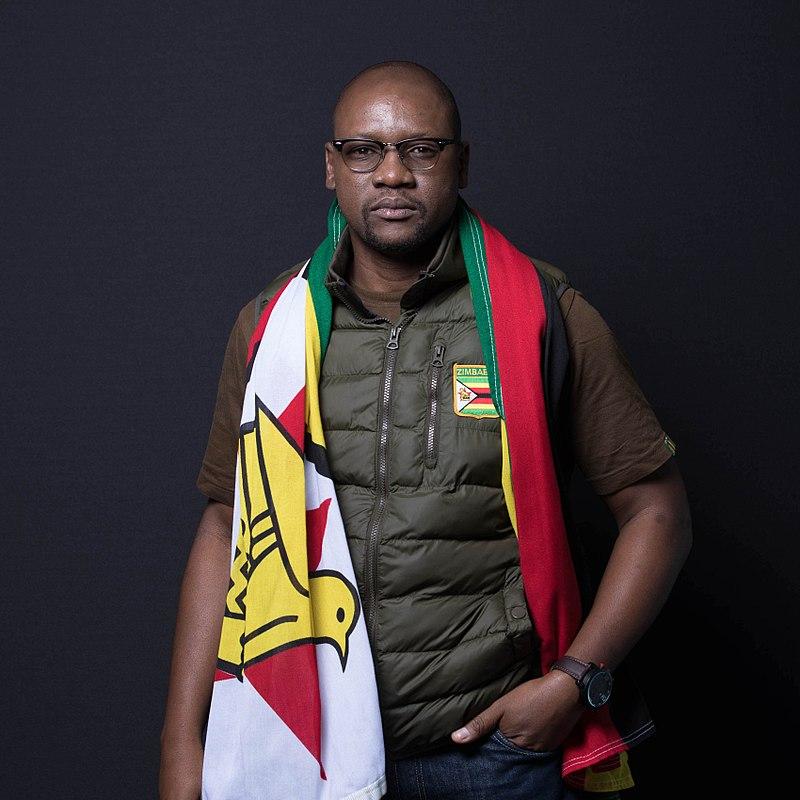 Evan Mawarire wears the Zimbabwean flag over his shoulders [ Wikimedia Commons ]
