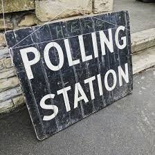 A polling station sign left on the ground (Pixabay).