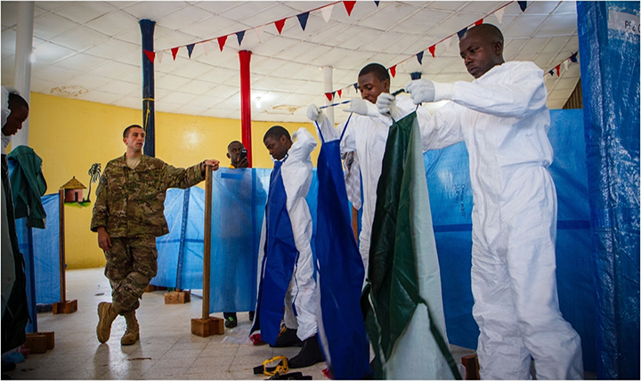 An American soldier oversees doctors kitting up for ebola treatment. (Military Health System)