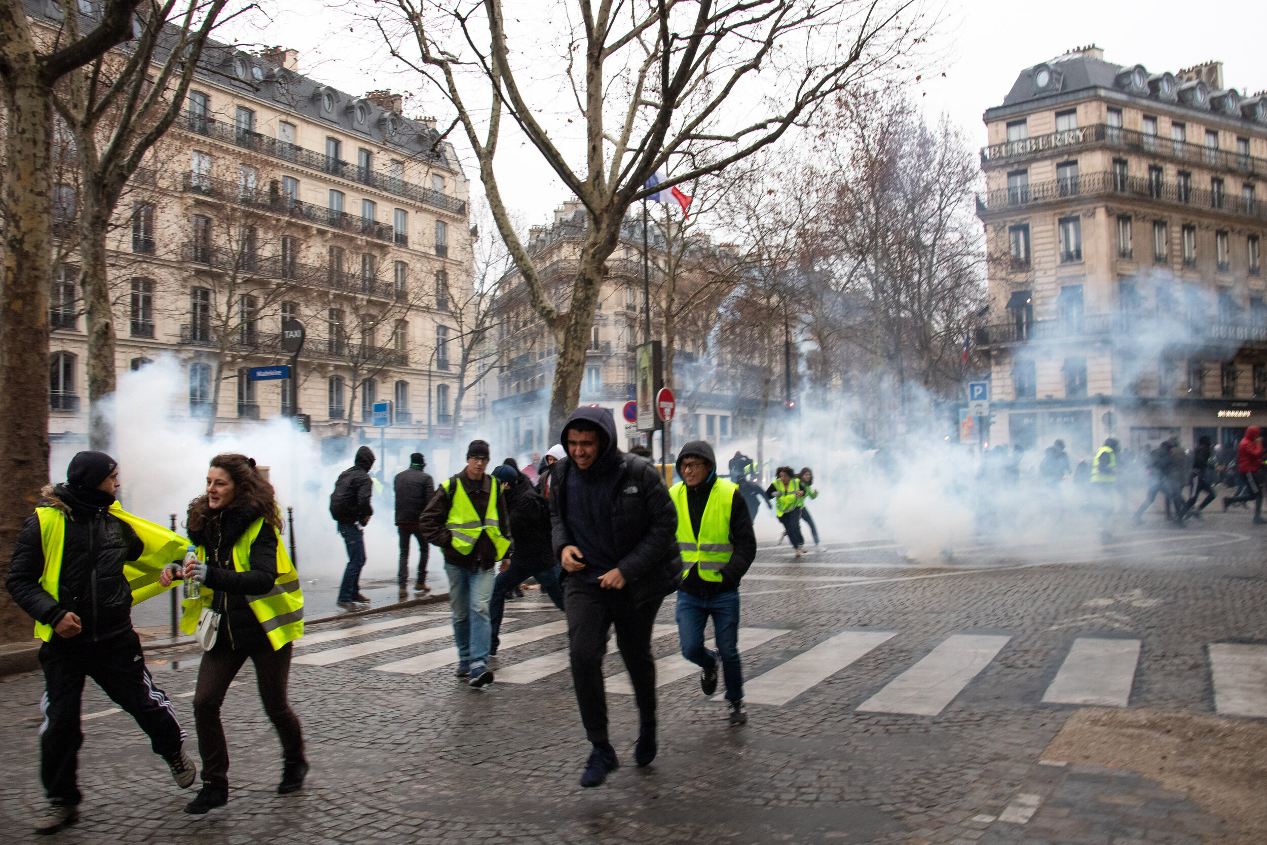 Yellow Vest protesters run from tear gas at an August 2018 protest. (Flickr)