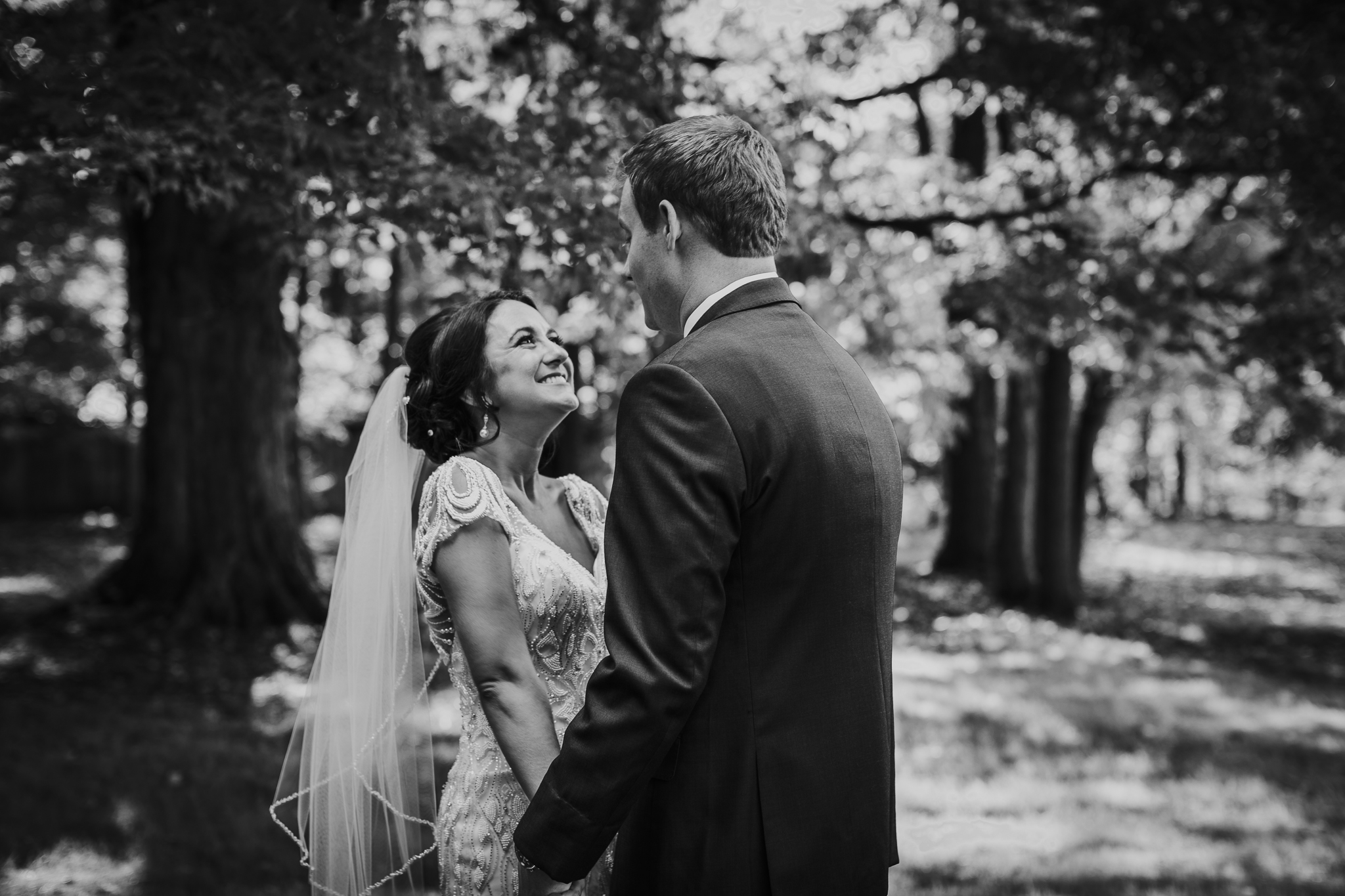 Bride smiles at groom in the woods