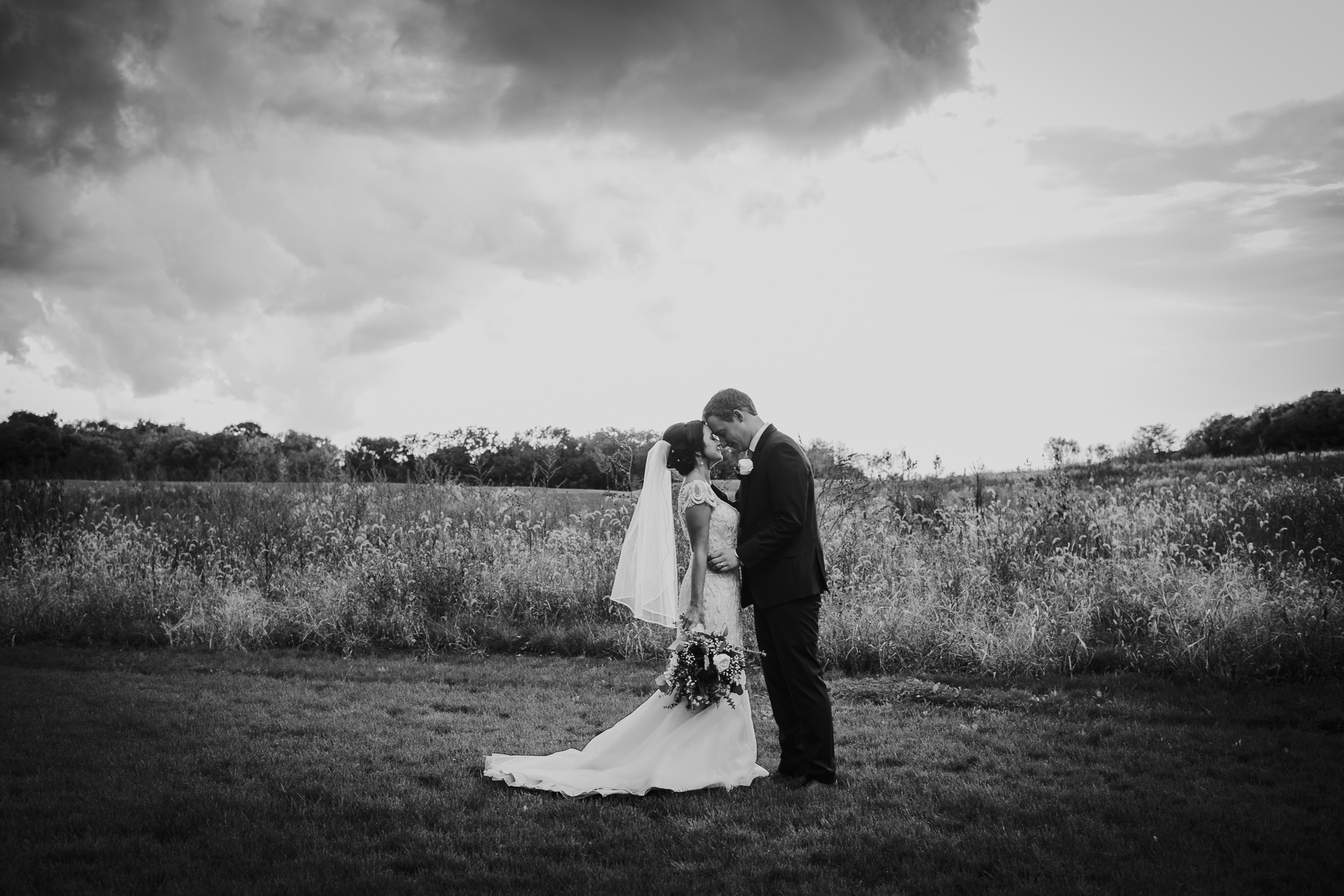 Bride & Groom embrace in field