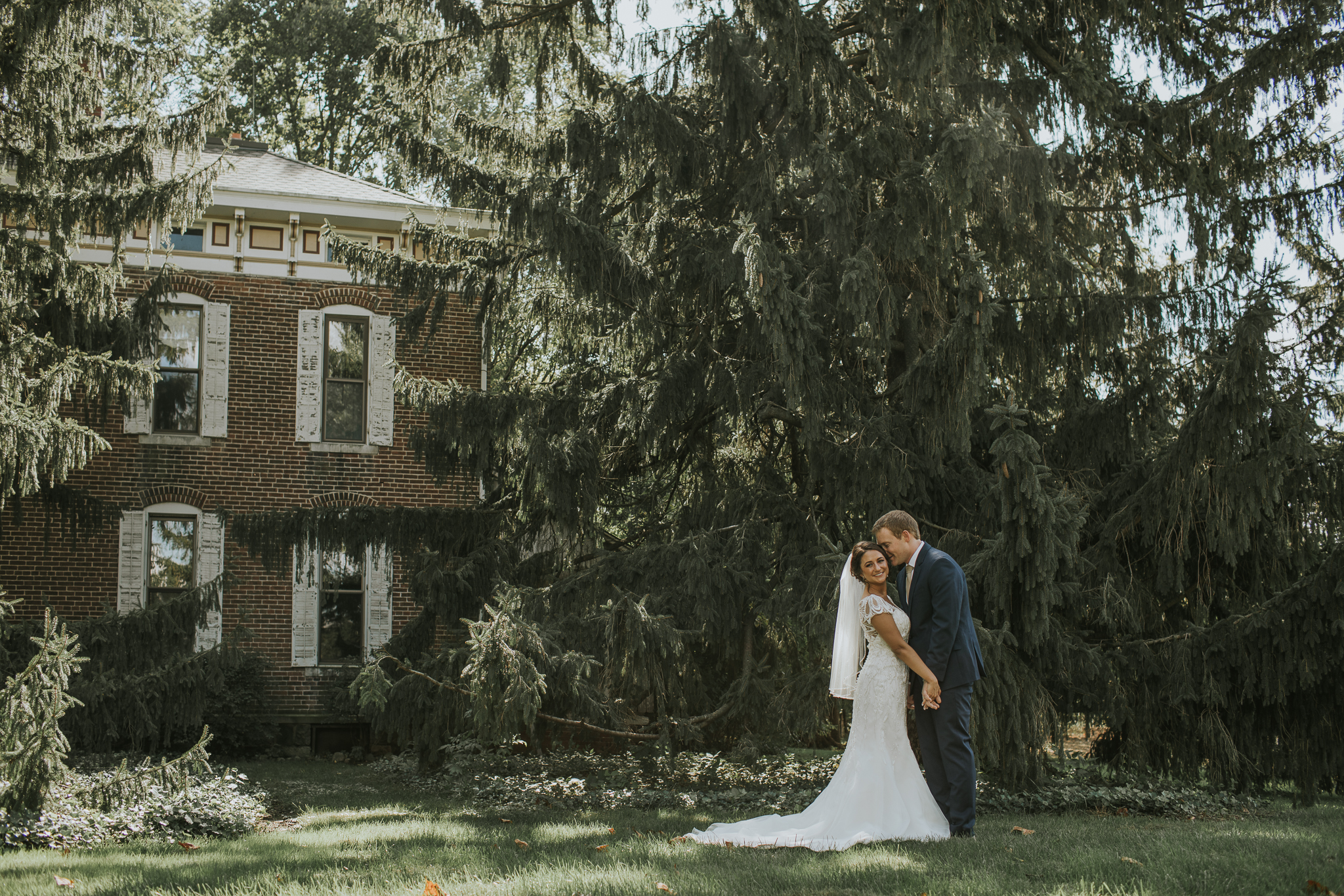bride and groom in front of house with large pine tree