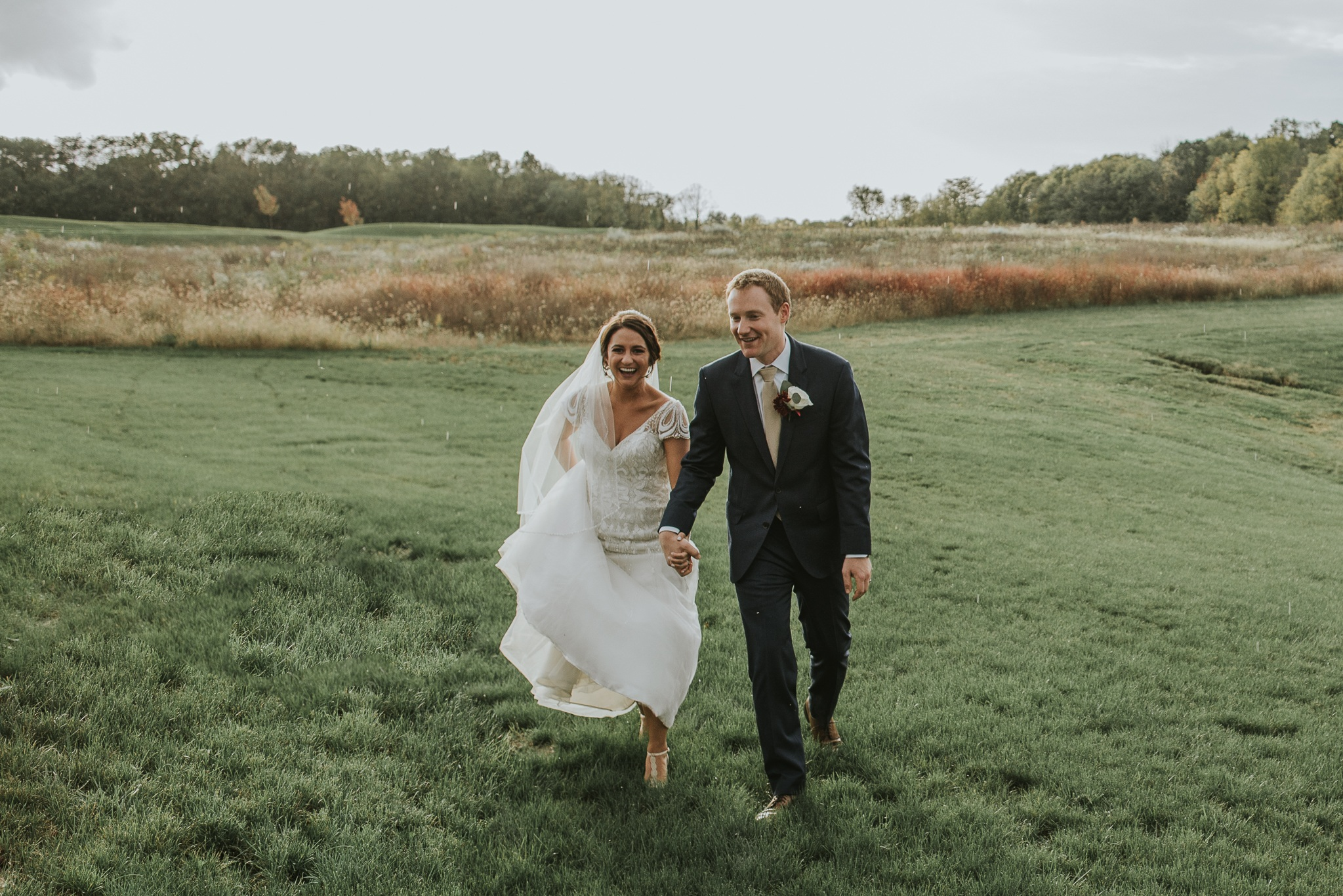 Bride & Groom walking through field while laughing