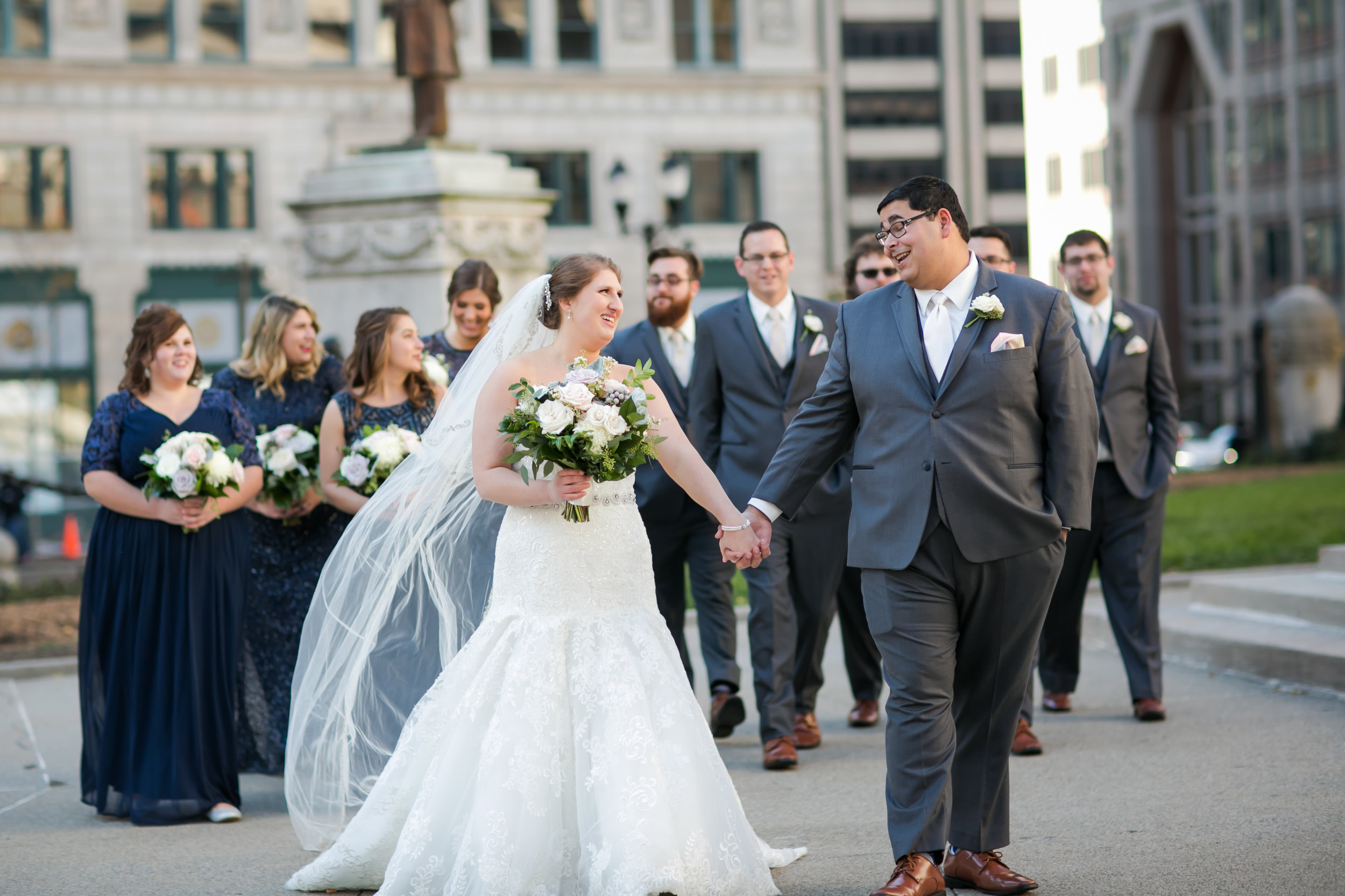 bride and groom walk downtown with bridal party