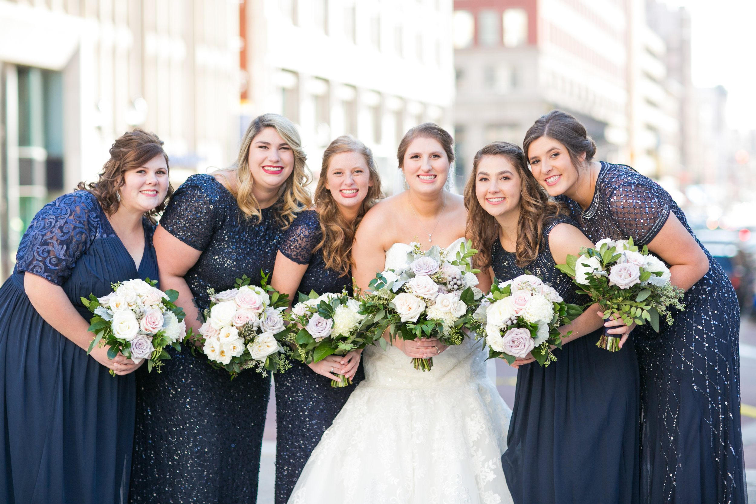 bride and bridesmaids smiling with bouquets downtown
