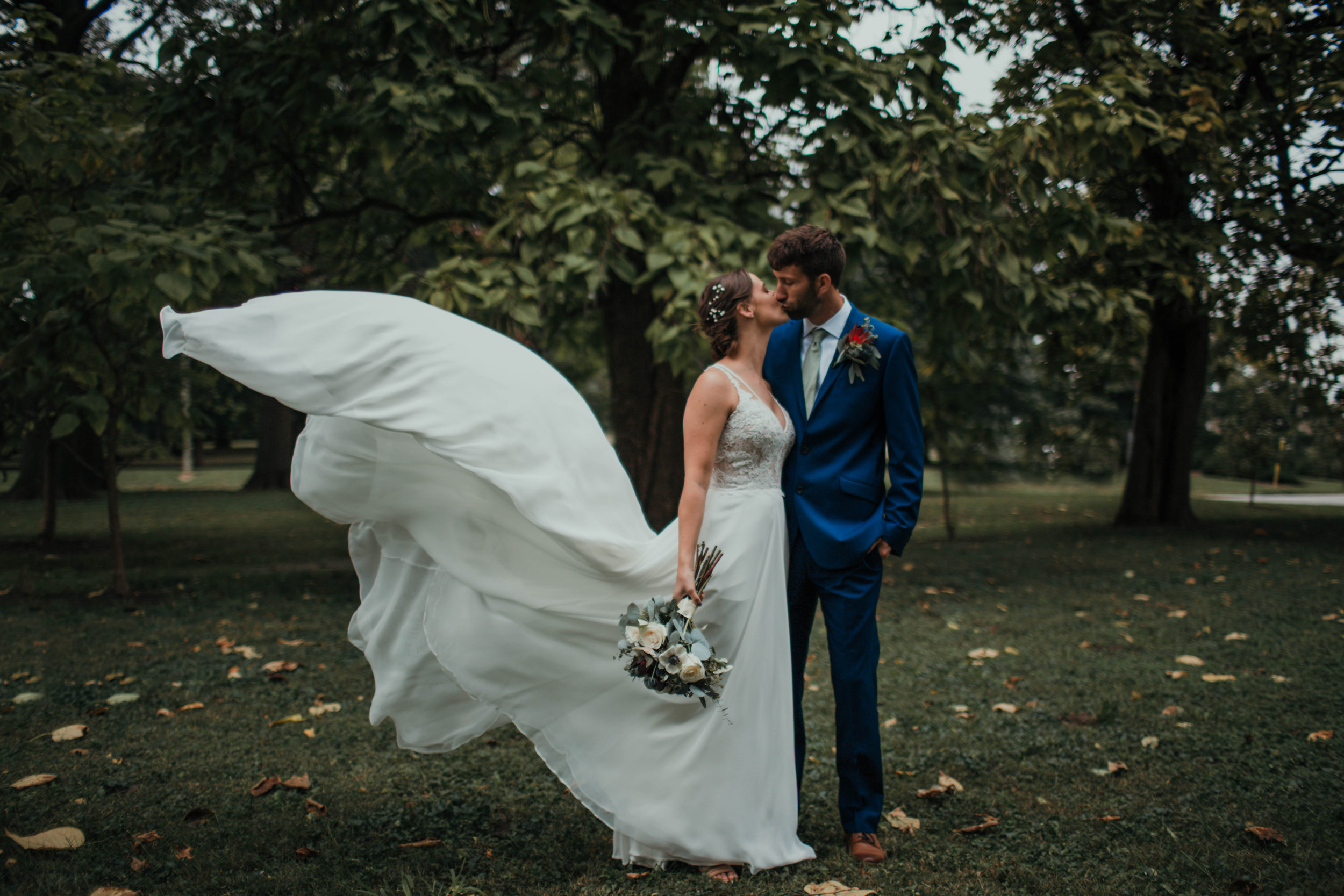 couple kisses while the bride's dress billows in the wind
