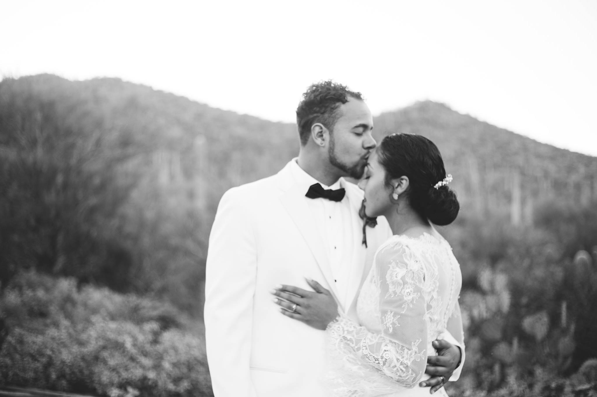 bride and groom kiss in the desert