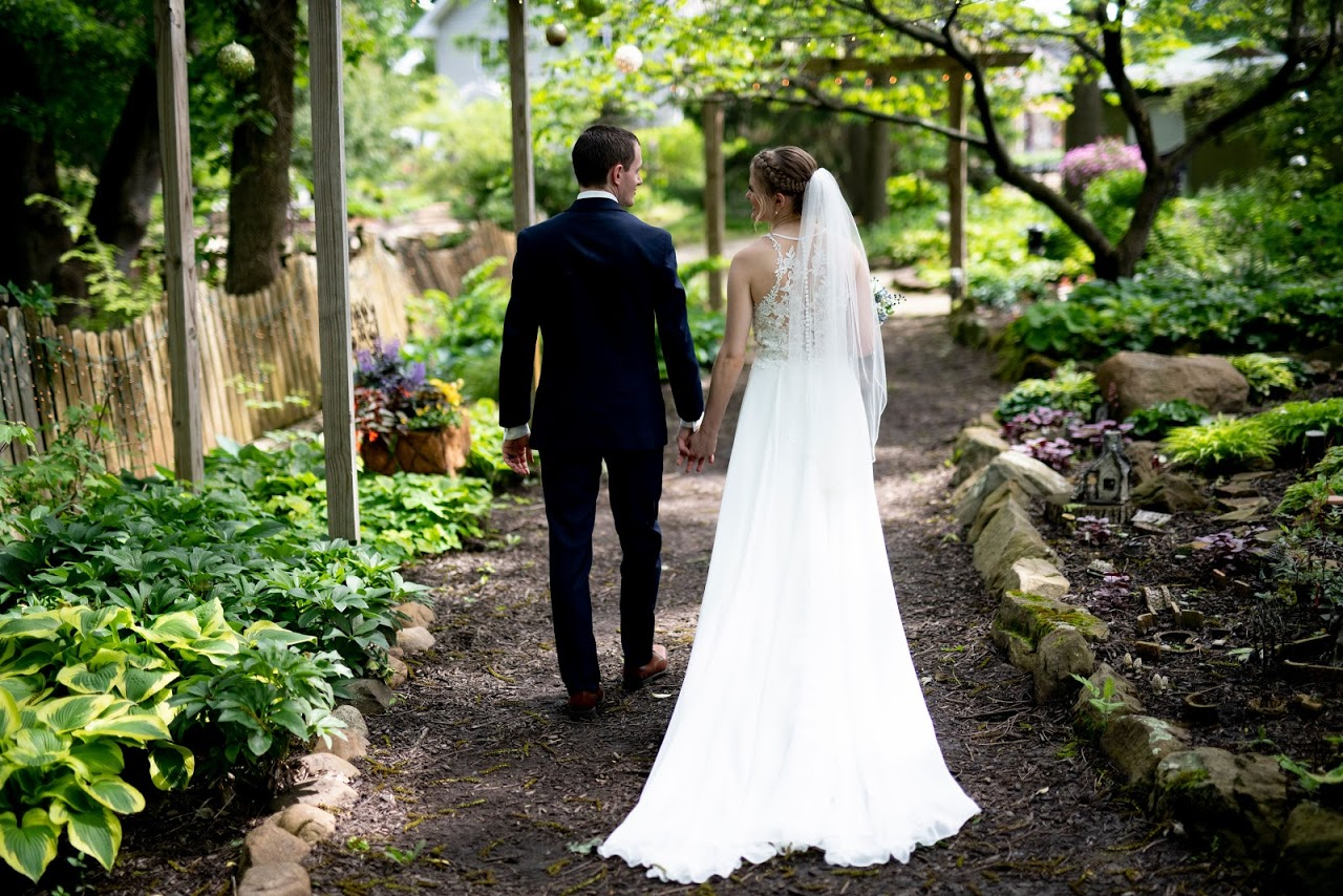 newlyweds walk through the garden hand in hand