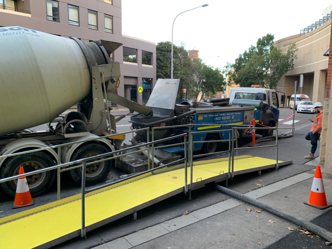 Our  pedestrian ramps  enable safe pedestrian access over concrete pumping lines. The hire of pedestrian ramps is especially useful on large developments in the Sydney CBD where large amounts of foot traffic is present during concrete pumps onto site for back filling and slab works. Due to this tripping hazard, council requires installation of safe and temporary access for pedestrians at the council approved angle.  Hiring a portable ramp also provides a cost effective and time saving alternative to manufacturing your own. They are also especially useful when diversion to another footpath or the other side of the road is not an option.