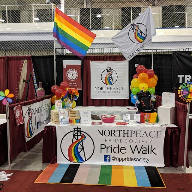 """Hey everyone!! Our booth is all decorated up and ready for the Fort St John Trade Show!! Come visit us at booth #34 where we will be promoting the 2019 """"Stronger Together"""" Pride Walk which will be happening on Saturday June 1st this year!! Also, during the Trade Show we are unveiling our brand new website!! Please swing by, we would love to talk to you.  You can even enter our free raffle for a backpack and gift cards to local businesses.  This year we are selling limited edition red t-shirts complete with our logo and 2019 Stronger Together design.  These red t-shirts will start of our exciting new  #completetherainbow challenge.  Every year leading up to the 10 year anniversary of our Pride Walk we will unveil a new t-shirt and each year will be a colour of the Pride rainbow!! T-shirts are $20.00 and we accept credit,debit and cash.  We look forward to seeing you at the Trade Show! #bcpeacepride #northpeacepridesociety #pridewalk2019 #fortstjohn #lgbt #priderainbow #strongertogether #fortstjohntradeshow #fsjpridewalk"""