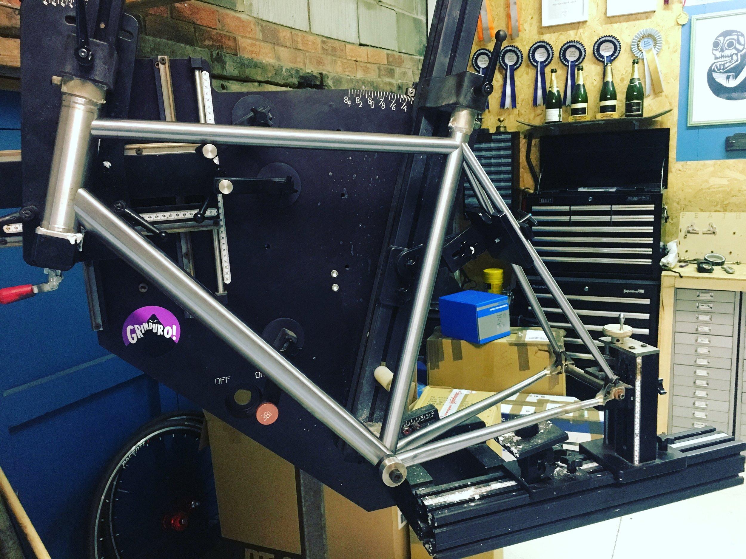 Mitred modern road bike frame in the frame fixture.