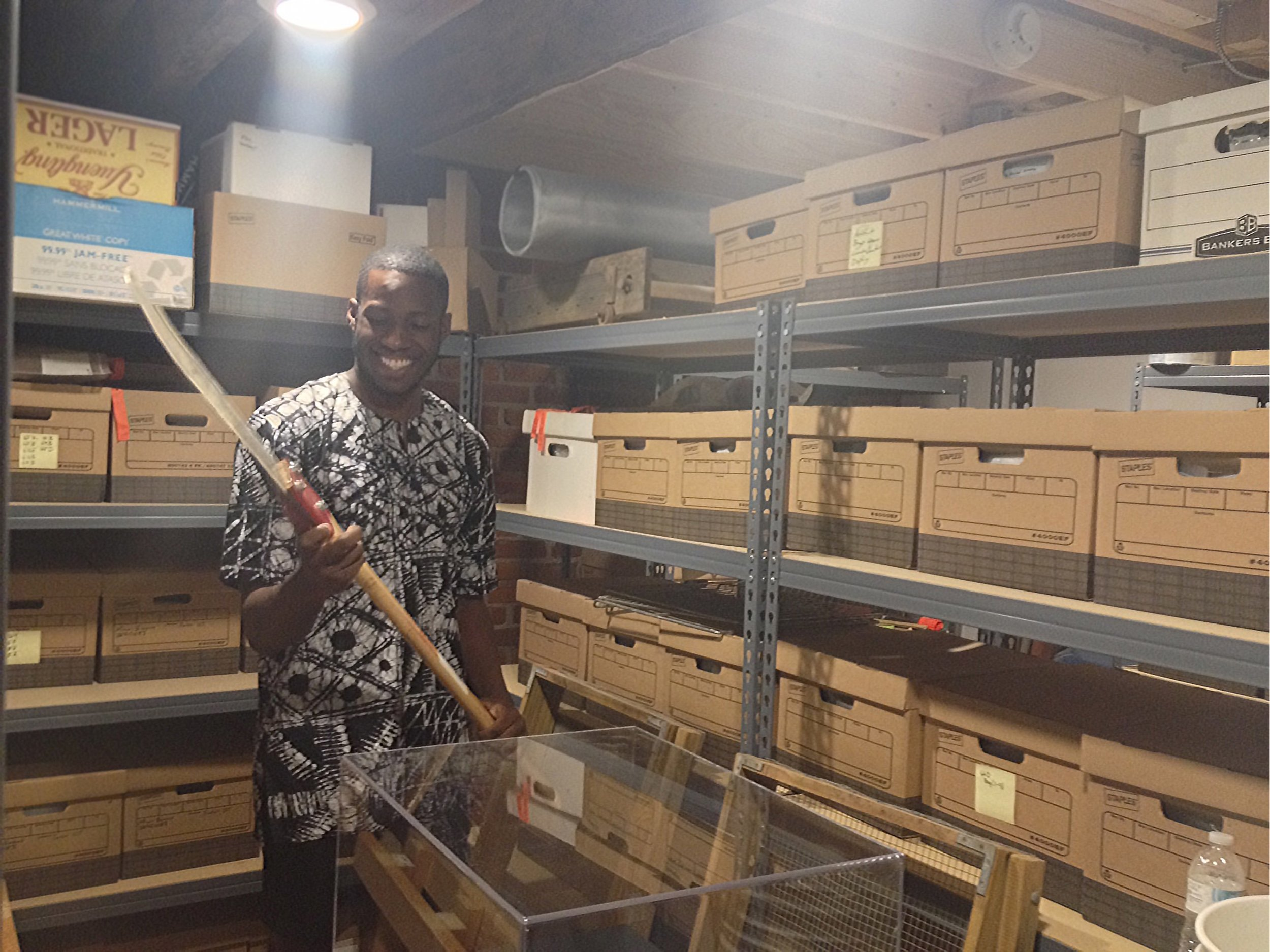 PCE Intern Isaac Udogwu holding archived farming tool.
