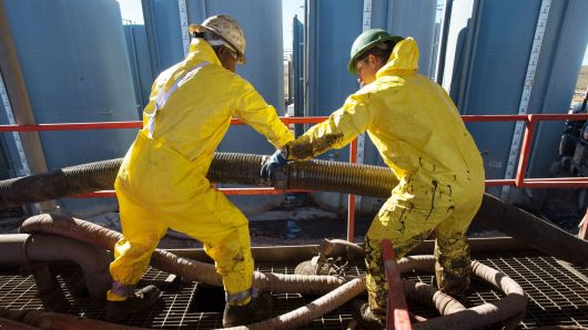 Ken Cedeno | Corbis | Getty Images Workers connecting tubes on the Raven Oil Drilling rig near Watford City N.D.
