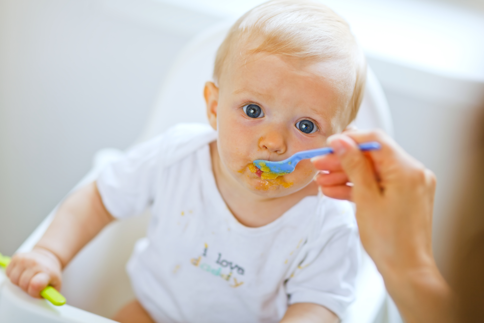 Eat smeared pretty baby eating from spoon