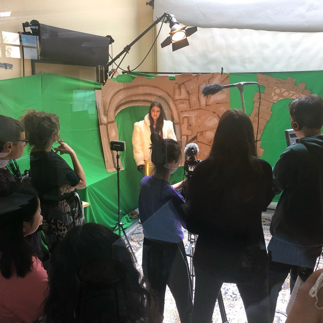 Filmmaking class filming using a green screen and backgrounds they designed