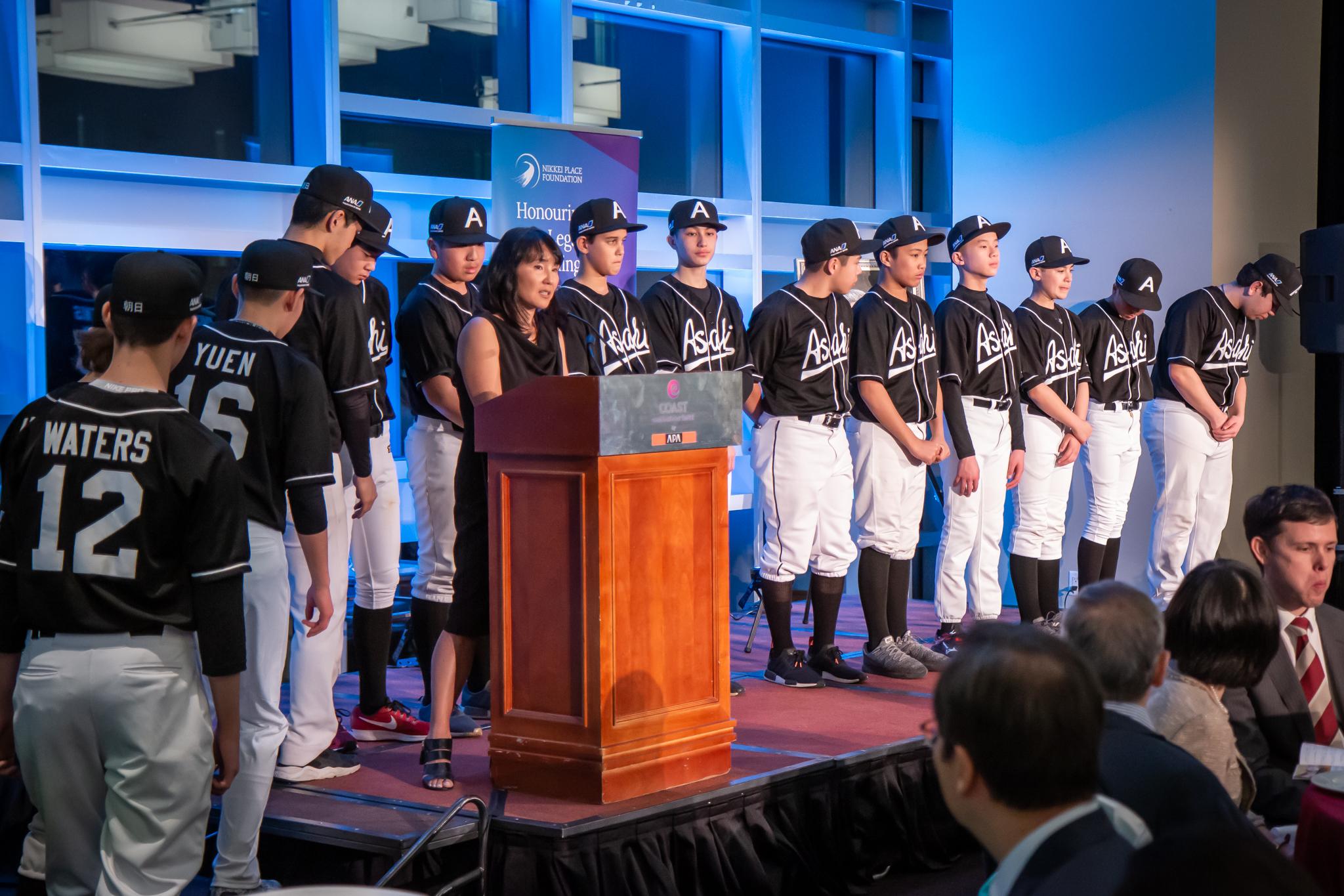 Emiko Ando of the Asahi Baseball Association accepts the Nikkei Youth Athletics Bursary on behalf of the Shin Asahi baseball team.
