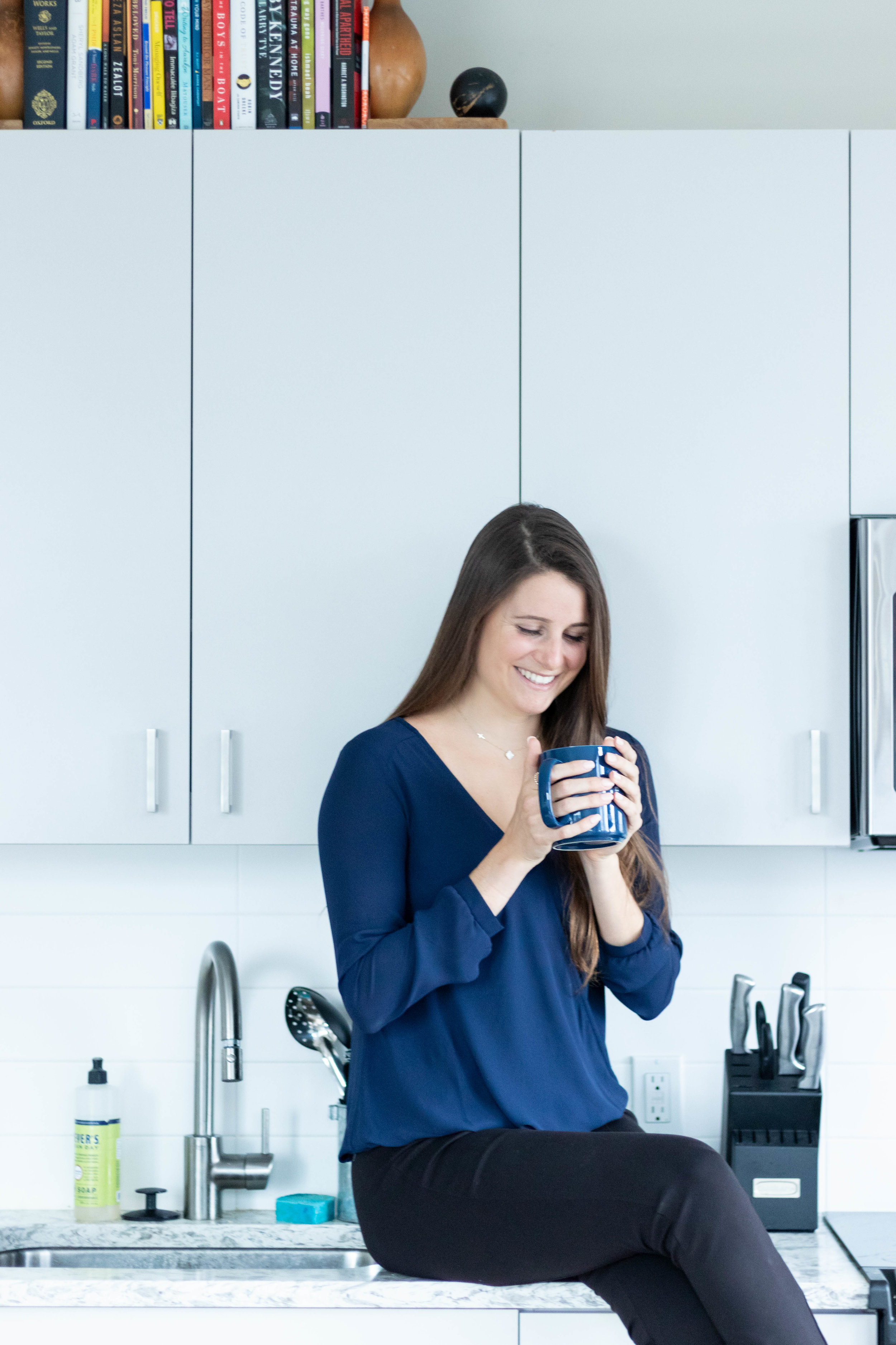 Lifestyle portrait photography of Erin Kenney from Nutrition Rewired registered dieititan holding a coffee mug and sitting on her kitchen counter photographed by Vision Balm in Charleston, SC.