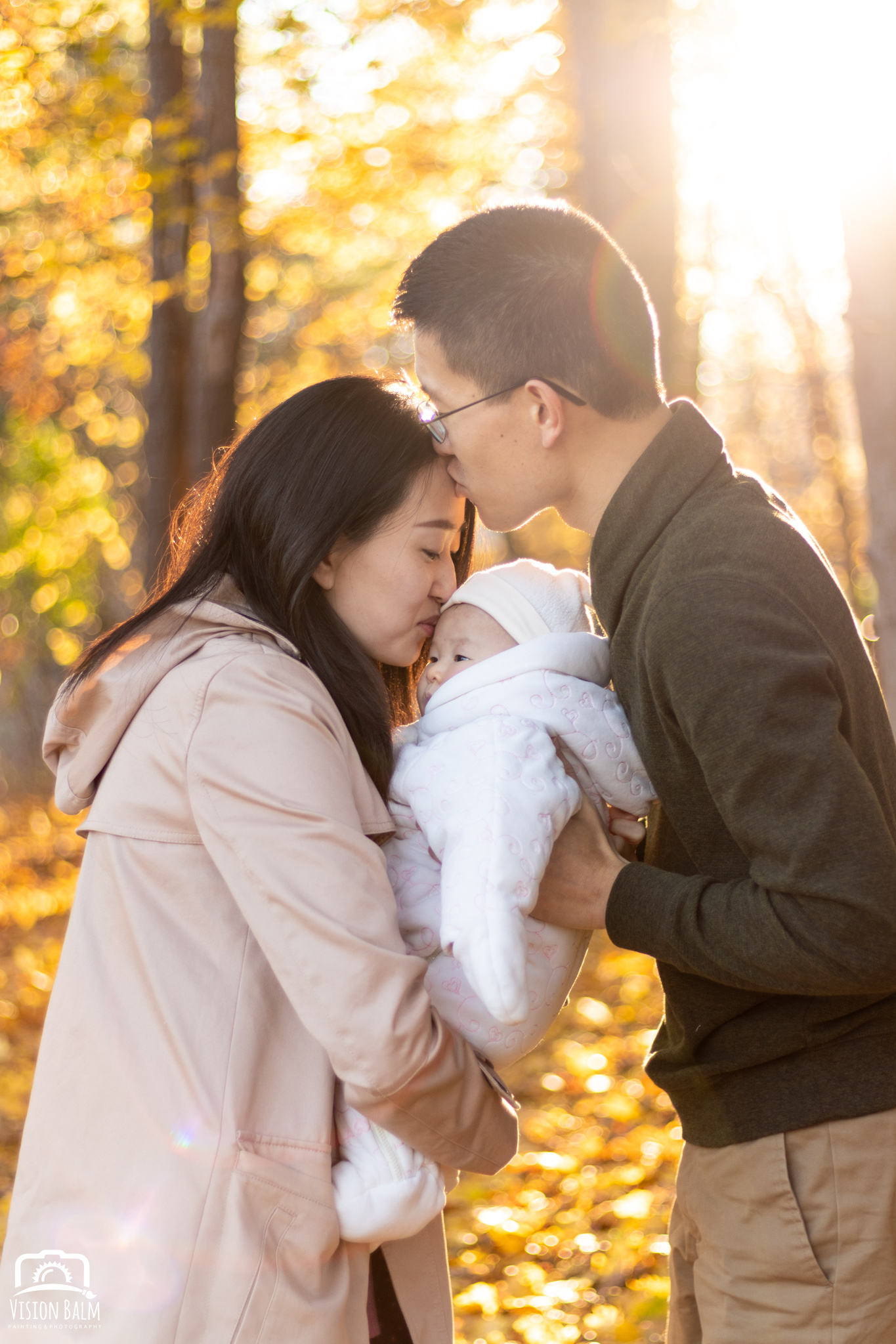 Family fall portrait of young couple with their baby kissing in the park photographed by Vision Balm in Charleston, SC.