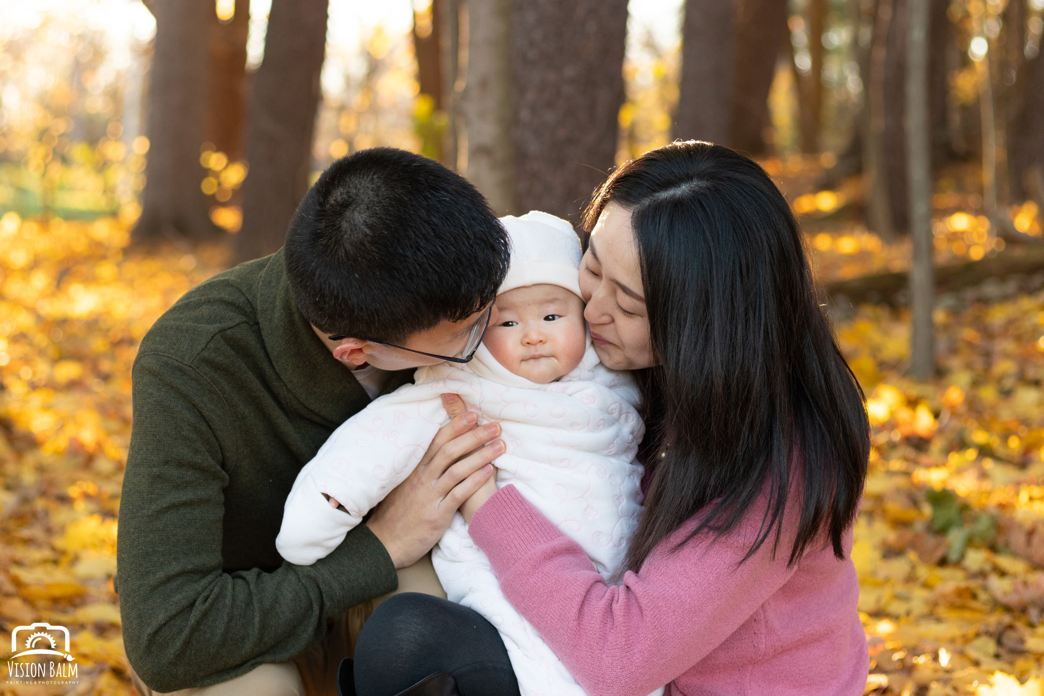 Family fall portrait of young couple with their baby in the park kissing photographed by Vision Balm in Charleston, SC.